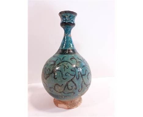 An Islamic Kashan turquoise glazed bottle vase decorated with a black scrolling foliate design with unglazed circular foot. H
