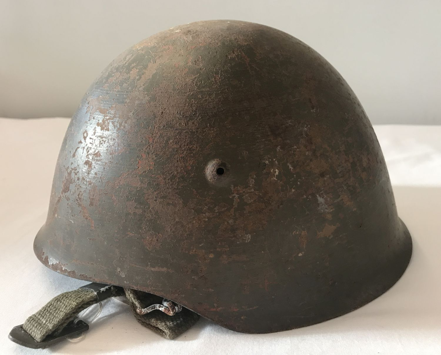 An M1940 - 63 Portuguese steel helmet, complete with canvas lining and chin strap.