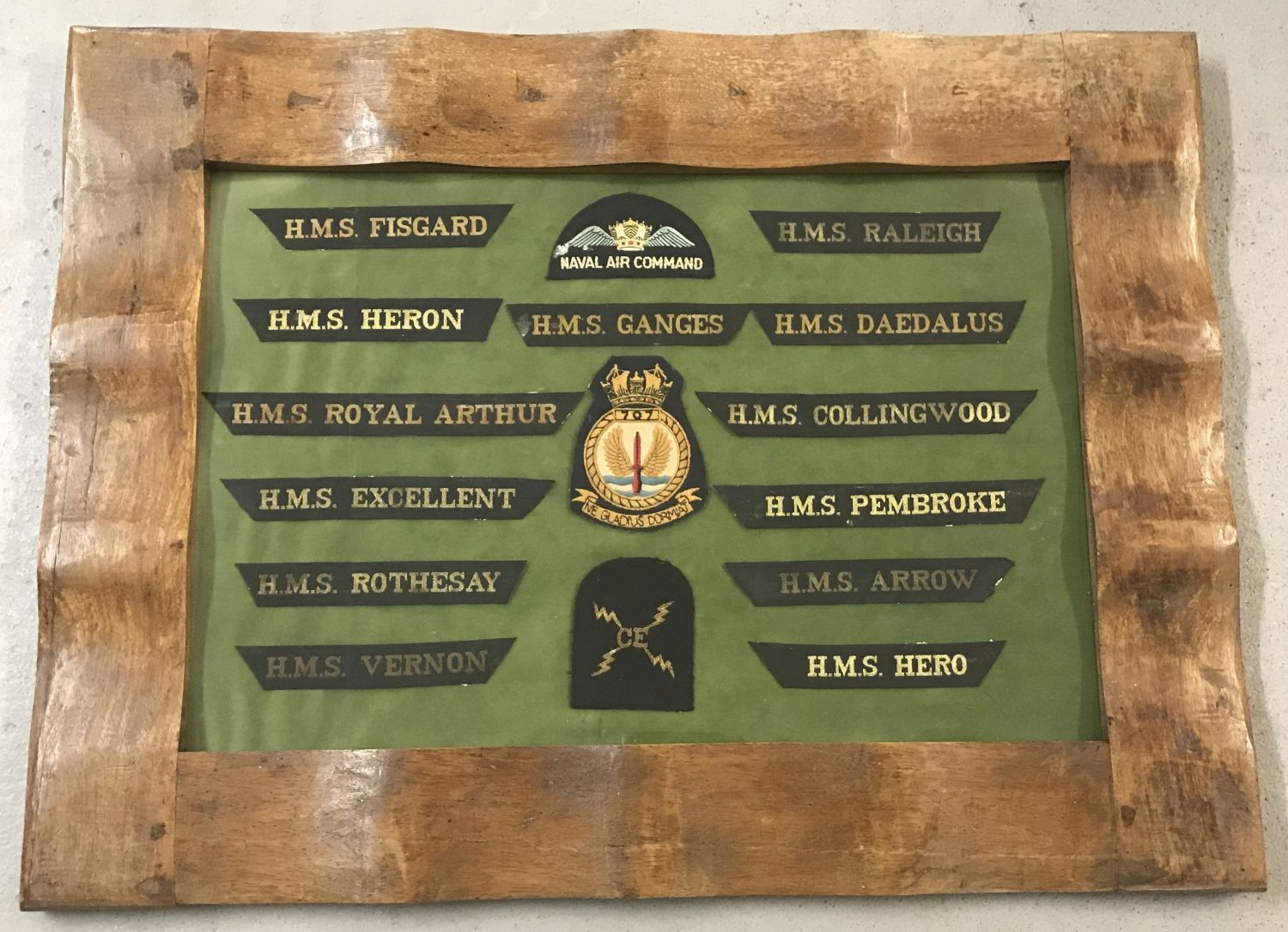 A framed and glazed mounted collection of Naval cap Tally's and cloth badges.