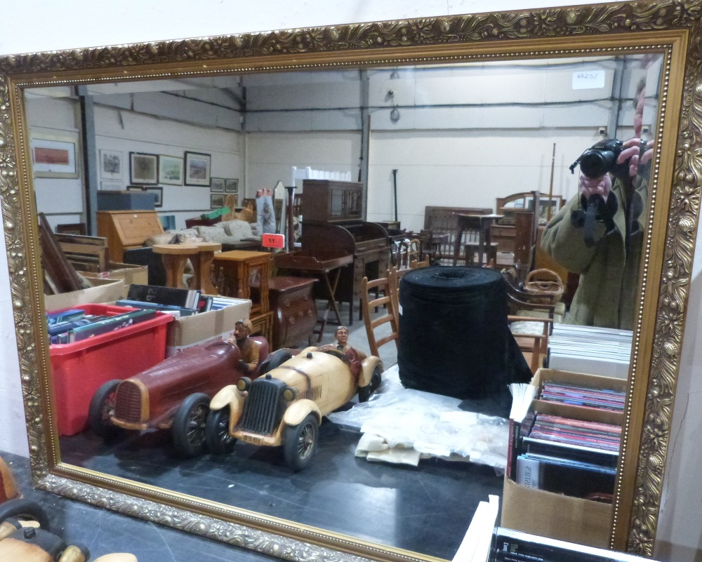 Lot 11 - A gilt framed wall mirror with bevelled plate. 48' wide