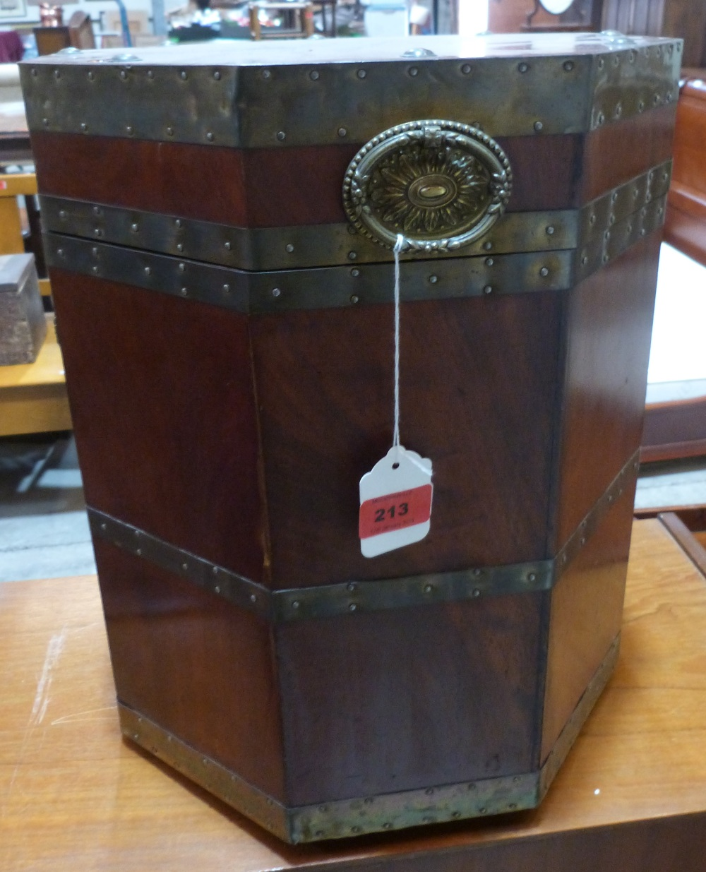 Lot 213 - A mahogany octagonal cellarette with brass straps and ring patera handles. 16 1/2' high