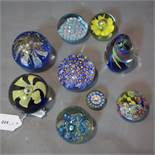 A collection of nine glass paperweights, to include millefiori examples, H.10cm (tallest)