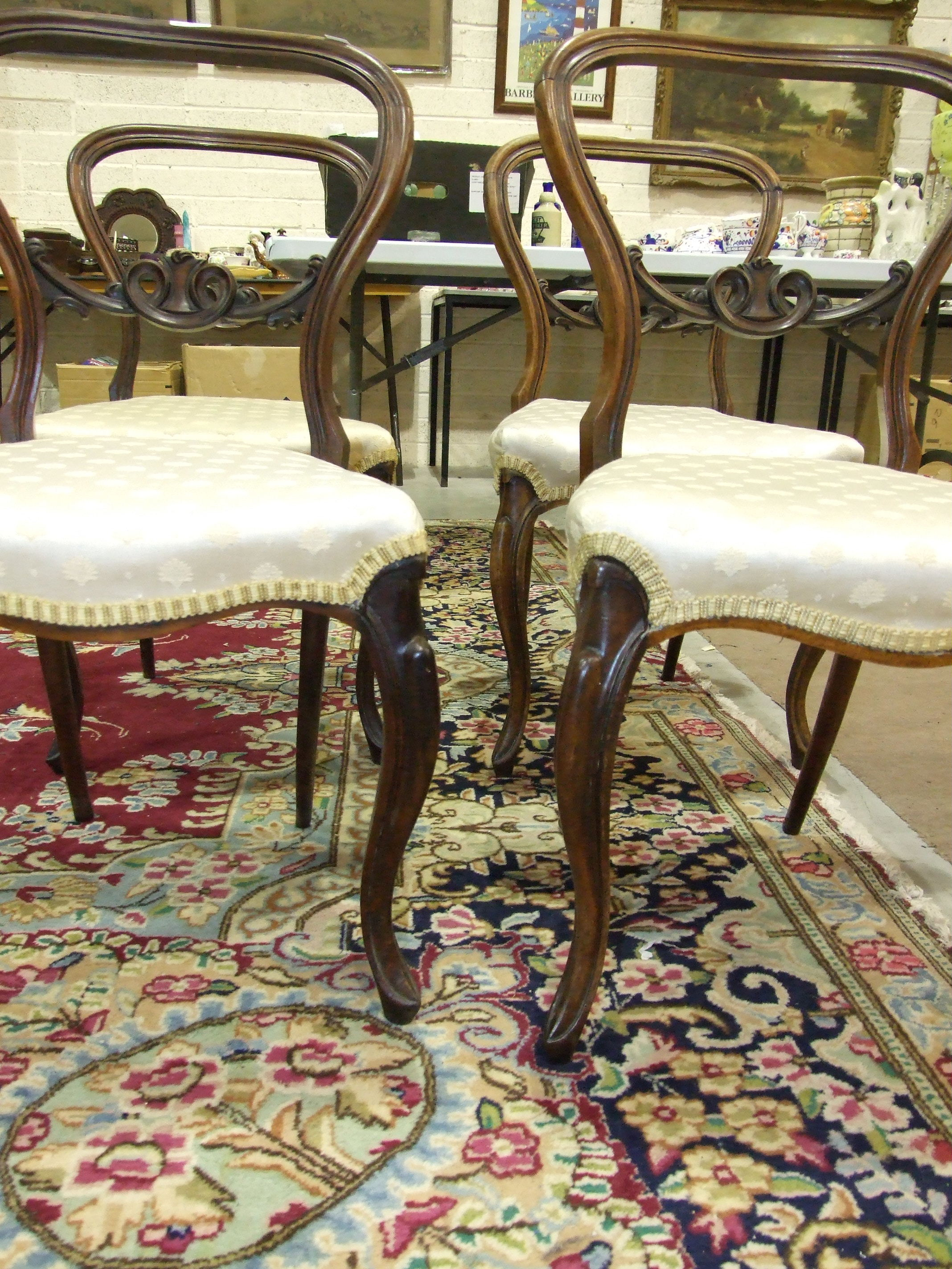 Lot 9 - A set of four rosewood Victorian balloon back dining chairs, each with carved centre rail,
