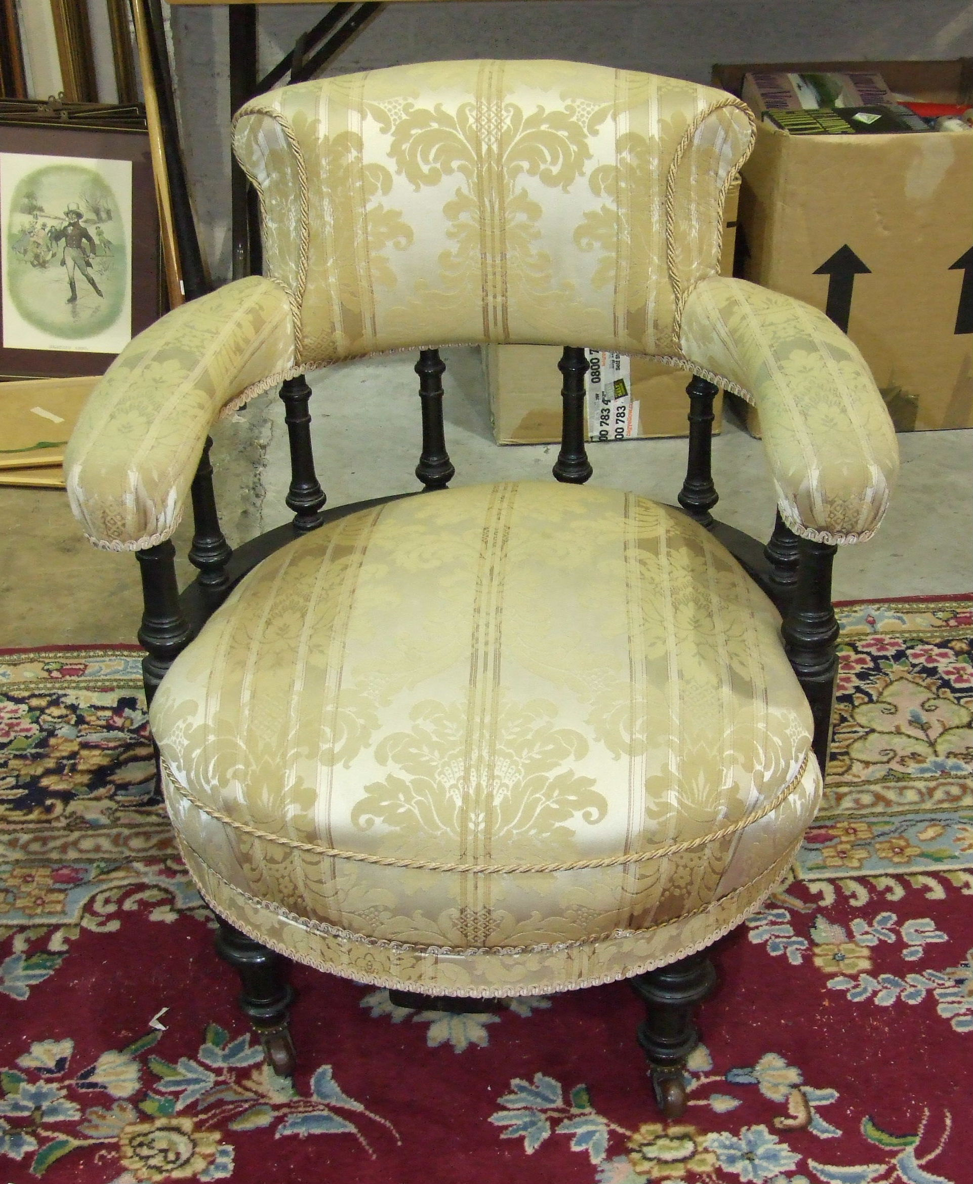 Lot 10 - A Late-Victorian ebonised tub armchair, the padded back and arms on turned supports above an