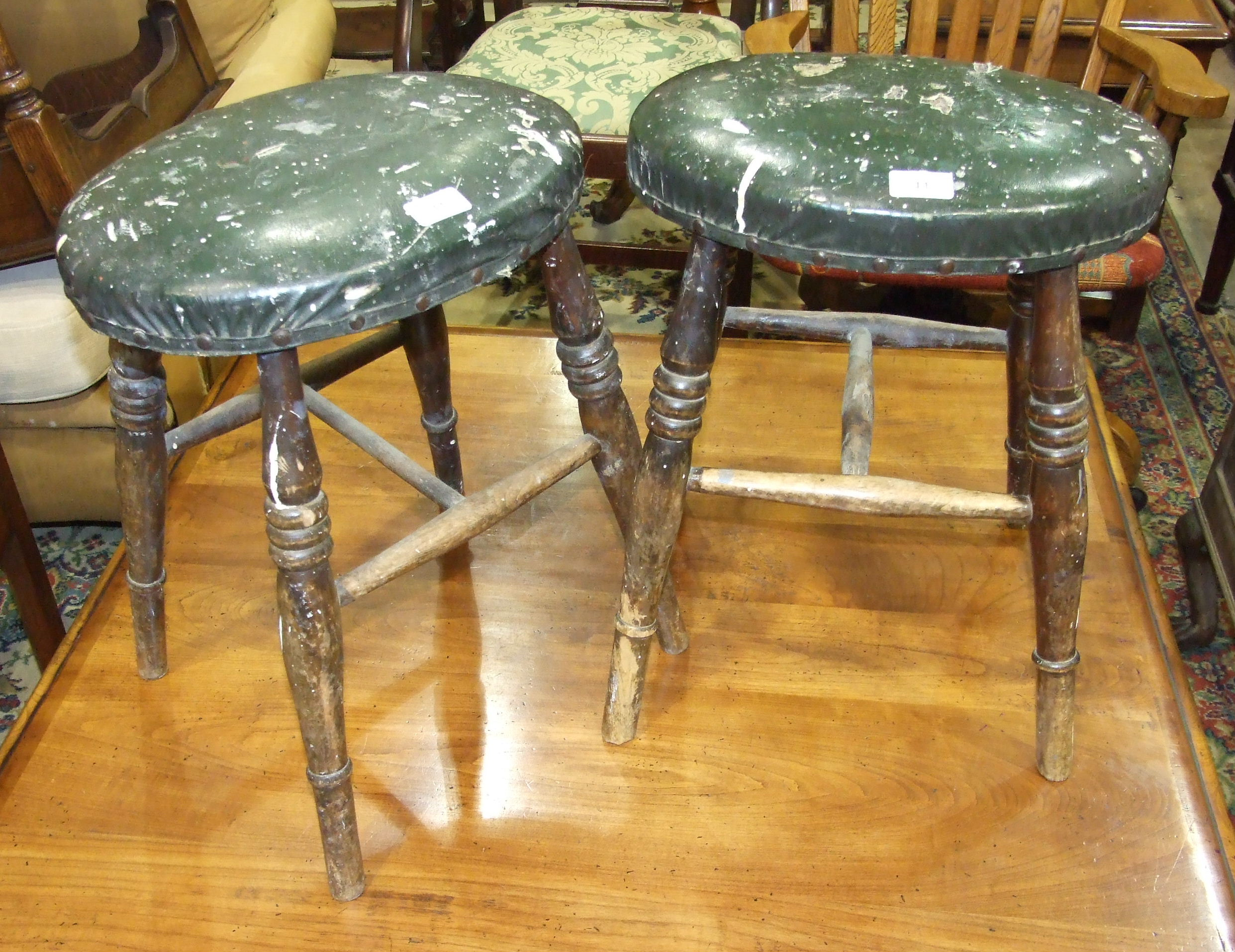 Lot 11 - A pair of late 19th/early 20th century stained beech oval seated stools with ring-turned legs,