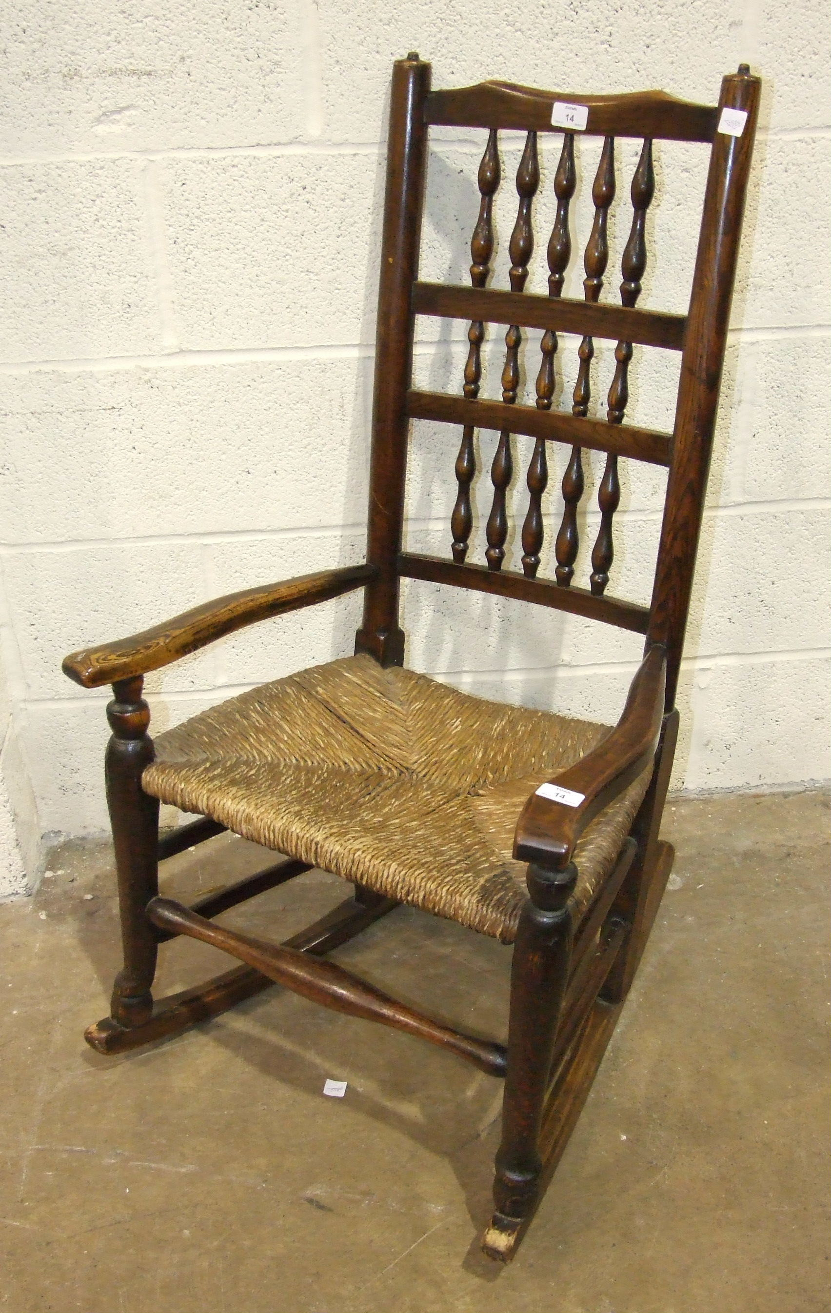 Lot 14 - A stained wood rocking chair with spindle back and rush seat.