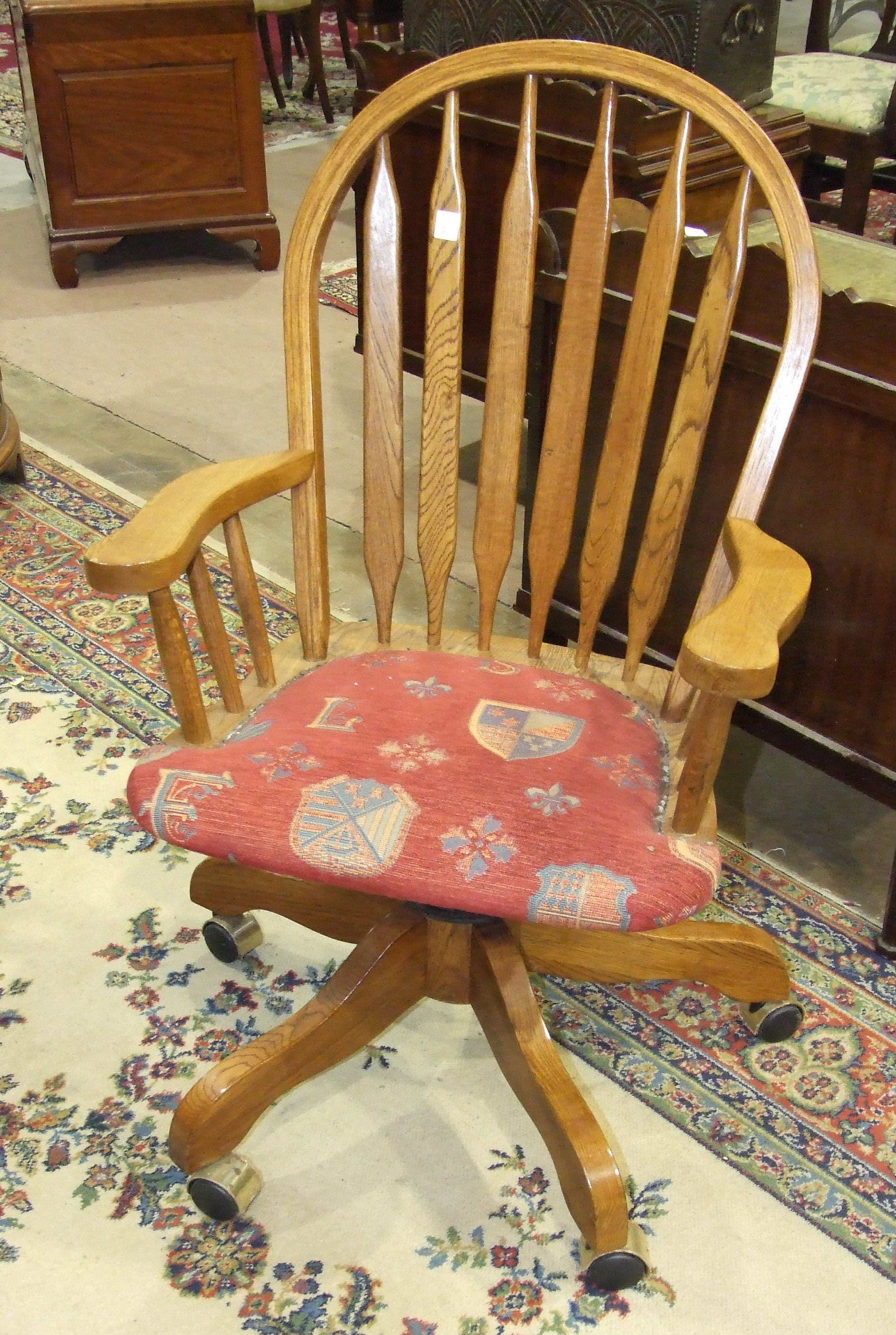 Lot 20 - A reproduction oak slat-back swivel office chair and an oak occasional table, (2).