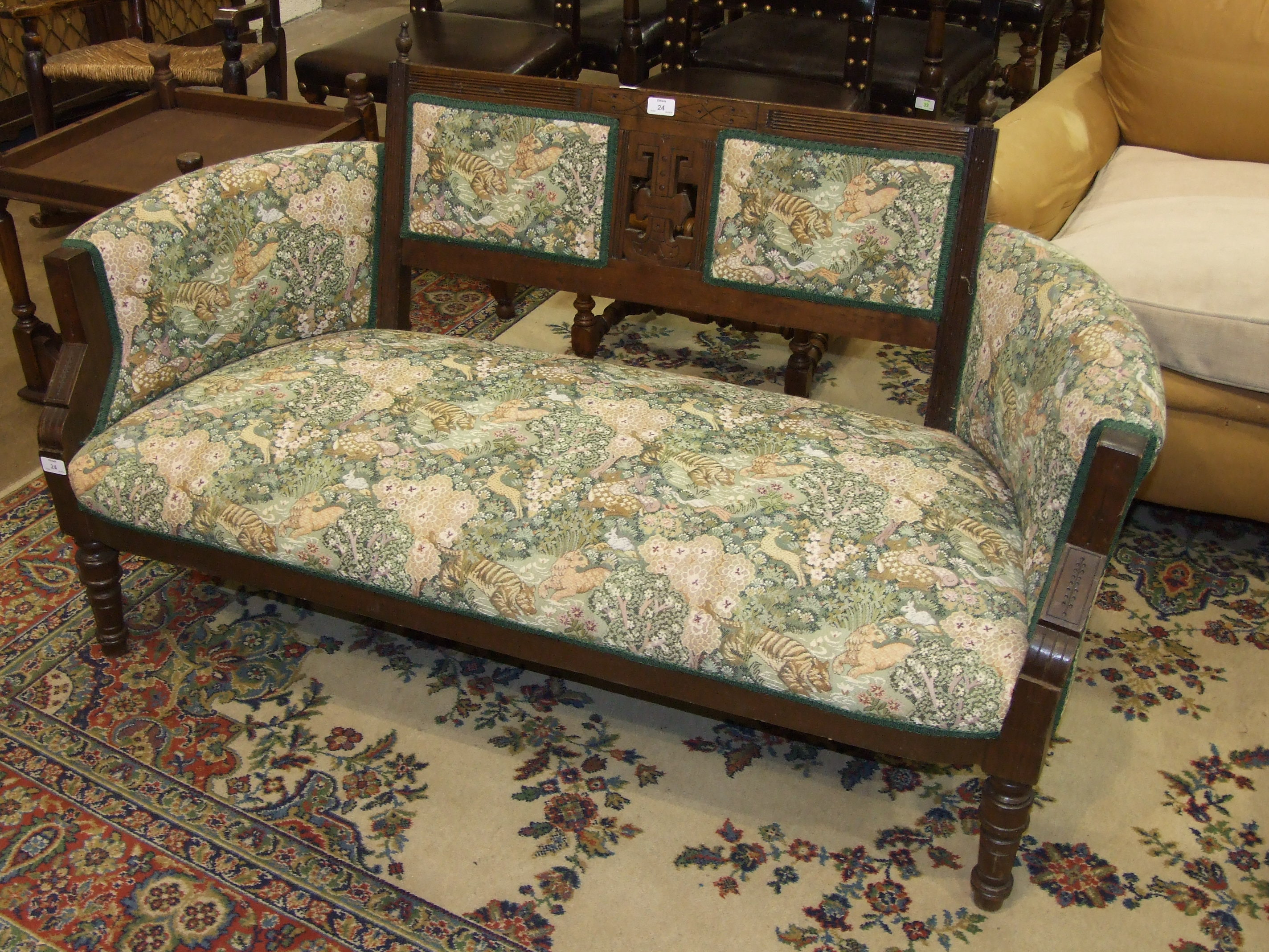 Lot 24 - An Edwardian mahogany frame two-seater settee with upholstered back, arms and seat, on turned