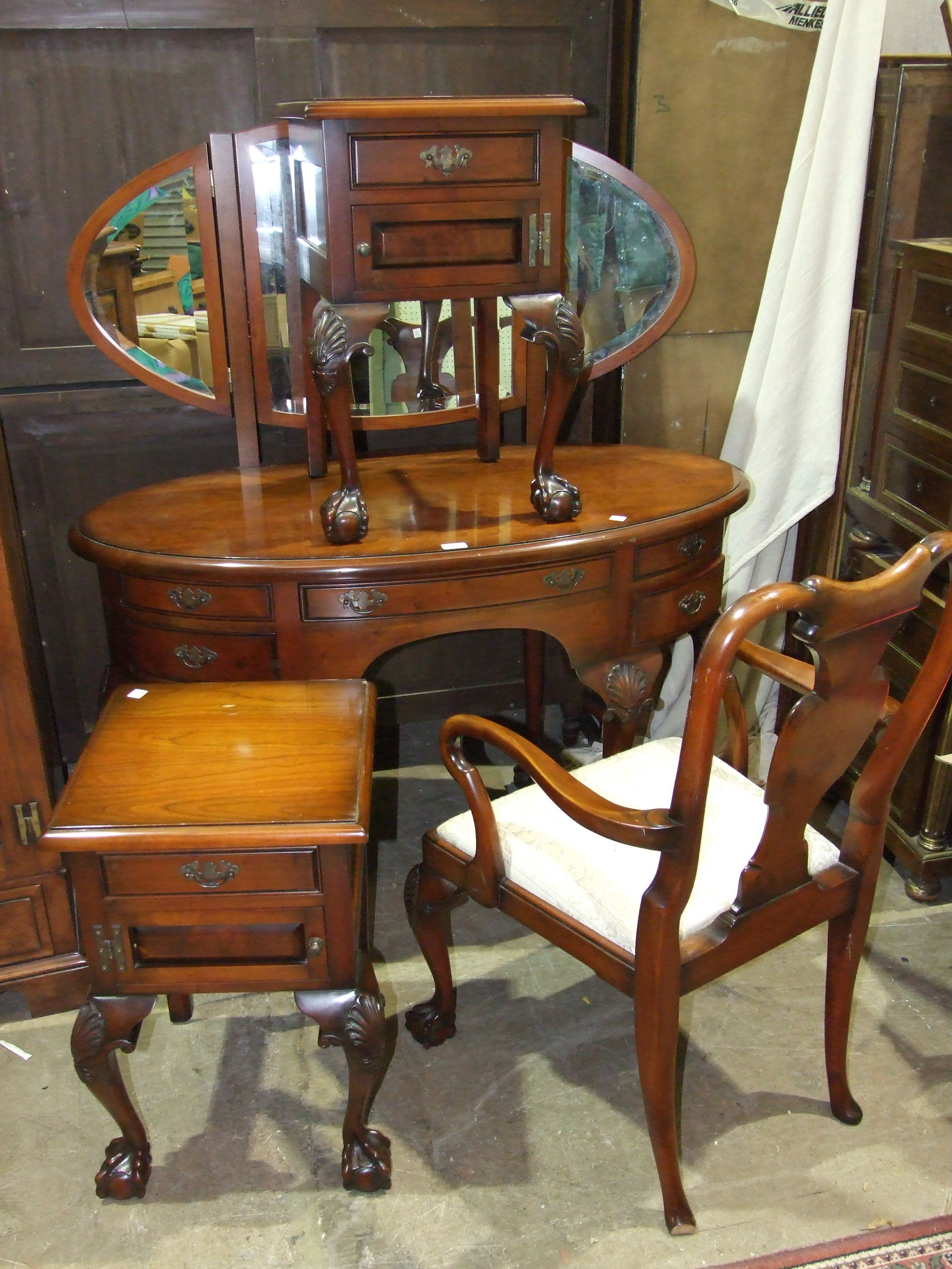 Lot 31 - A modern mahogany finish dressing table, the triple mirror above an oval top and five drawers, on