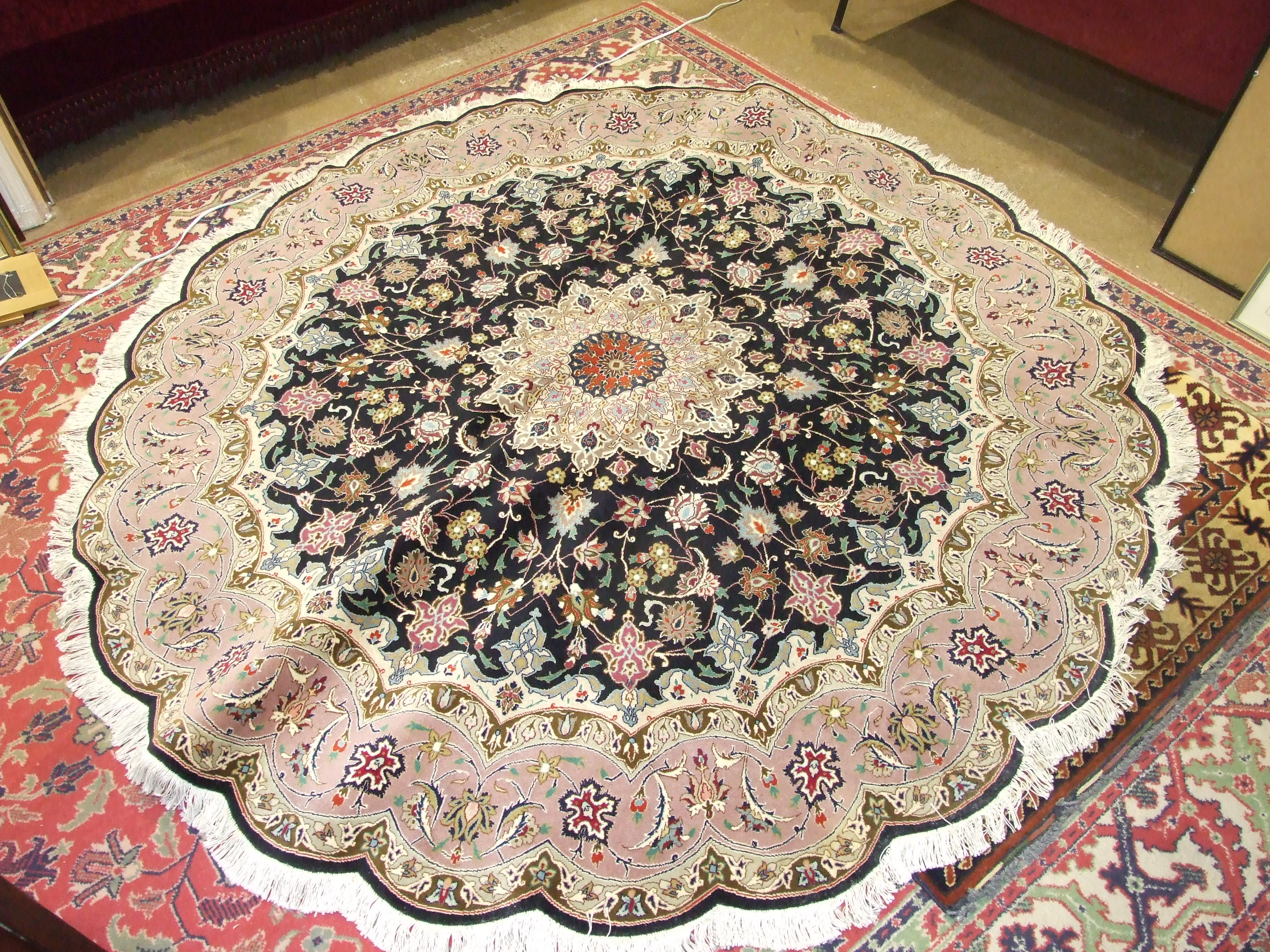 A modern Tabriz circular wool rug with scalloped edge, salmon pink border and foliate design on a