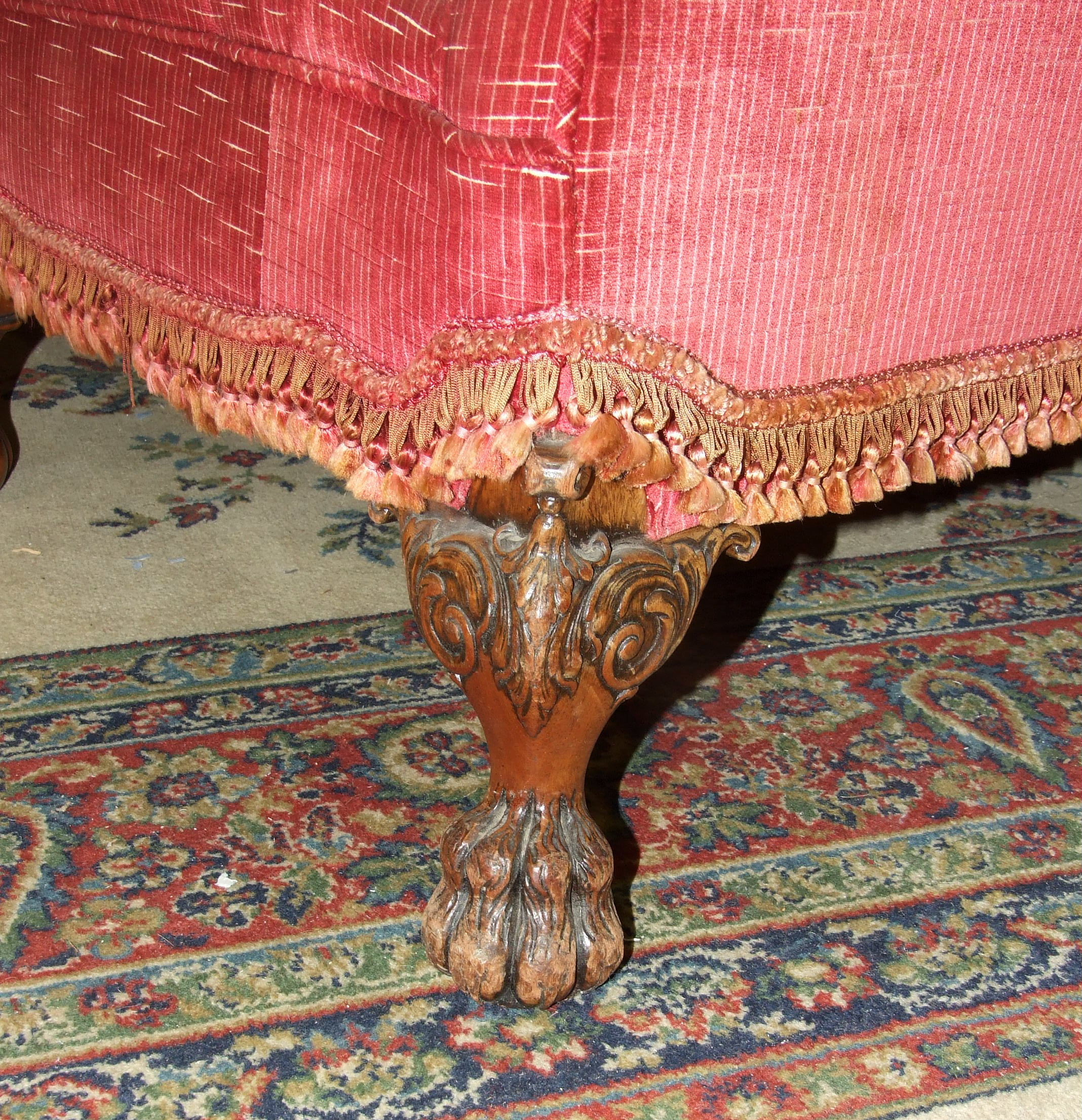 Lot 13 - An early 20th century upholstered deep-seated three-seater settee with carved front feet, and a pair