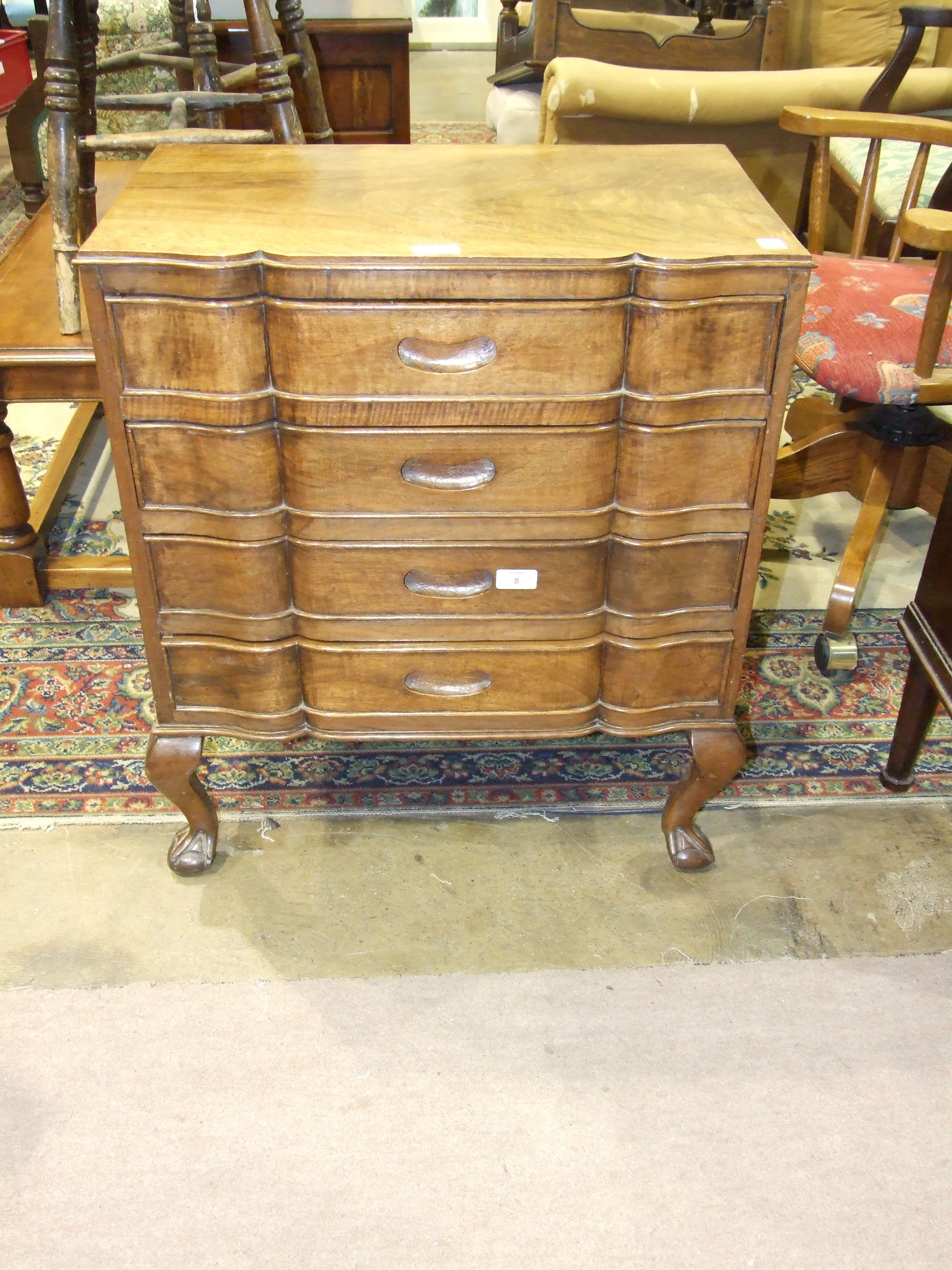 Lot 8 - A low walnut chest, the shaped top above four drawers, on short cabriole legs and claw and ball