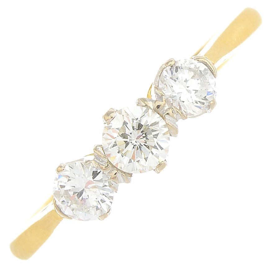 An 18ct gold diamond three-stone ring.Estimated total diamond weight 0.50ct,