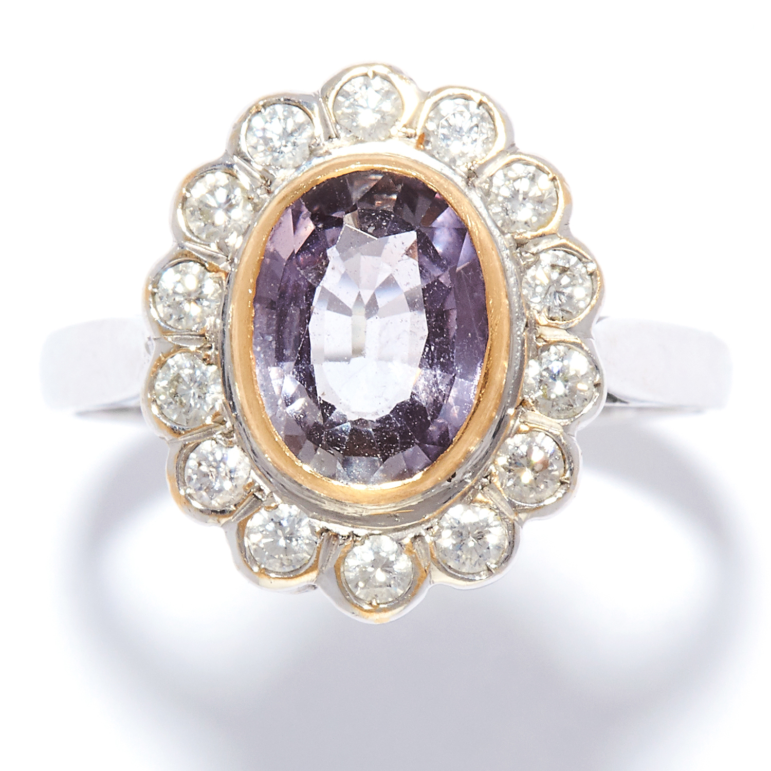 PURPLE SAPPHIRE AND DIAMOND CLUSTER RING in 18ct white gold, set with an oval cut purple sapphire of