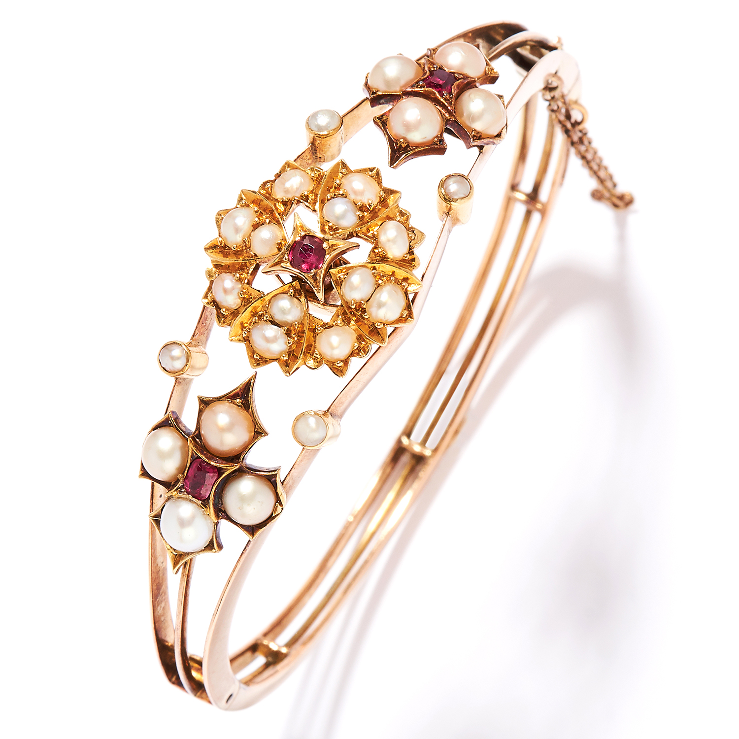 ANTIQUE PEARL AND RUBY BANGLE in 18ct yellow gold, the split, openwork design set with ruby and