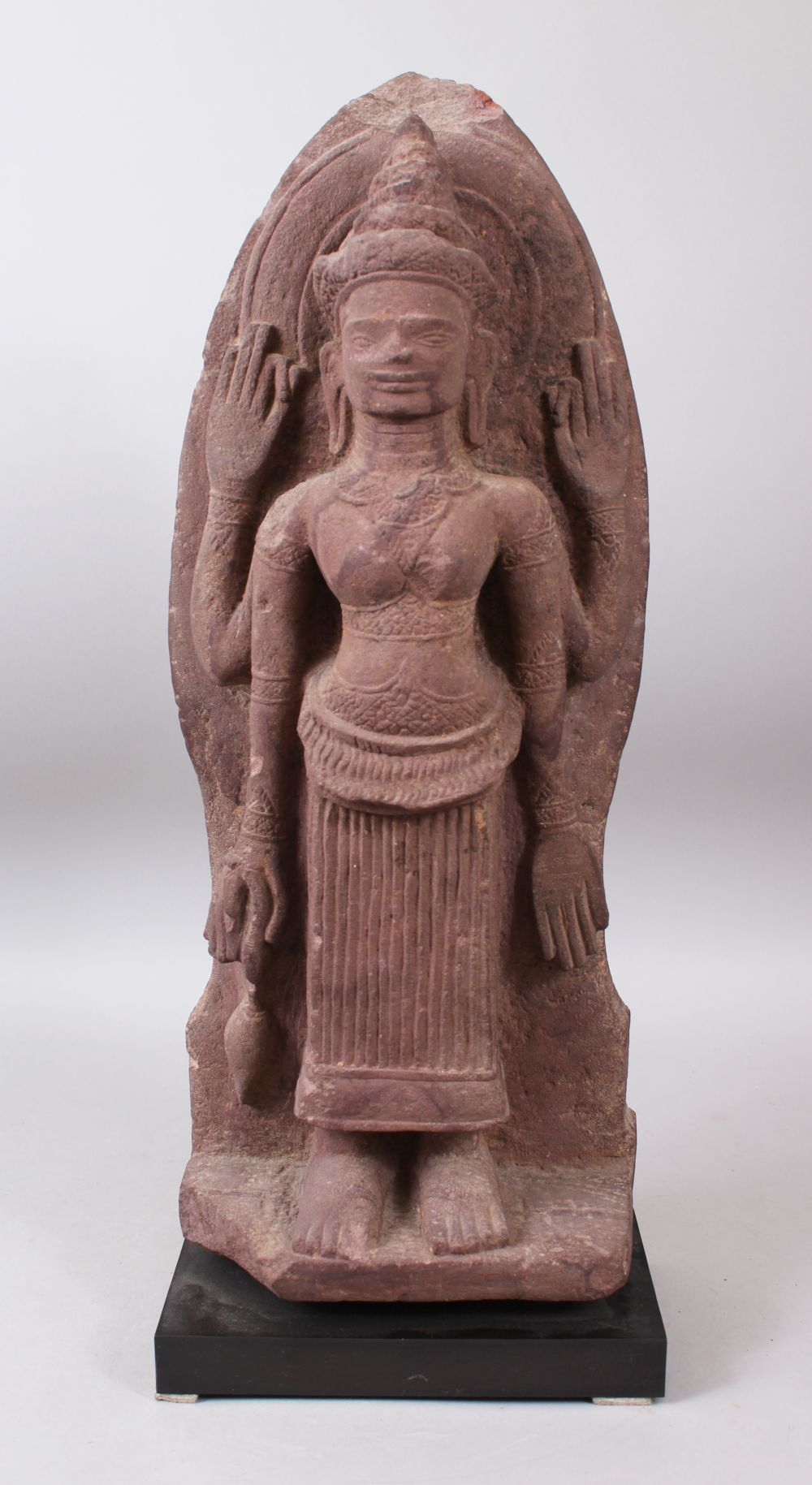 Lot 481 - A 12TH CENTURY STYLE CAMBODIAN KHMER STYLE RED SANDSTONE CARVING OF A FOUR ARMED DEITY. 52cms high.