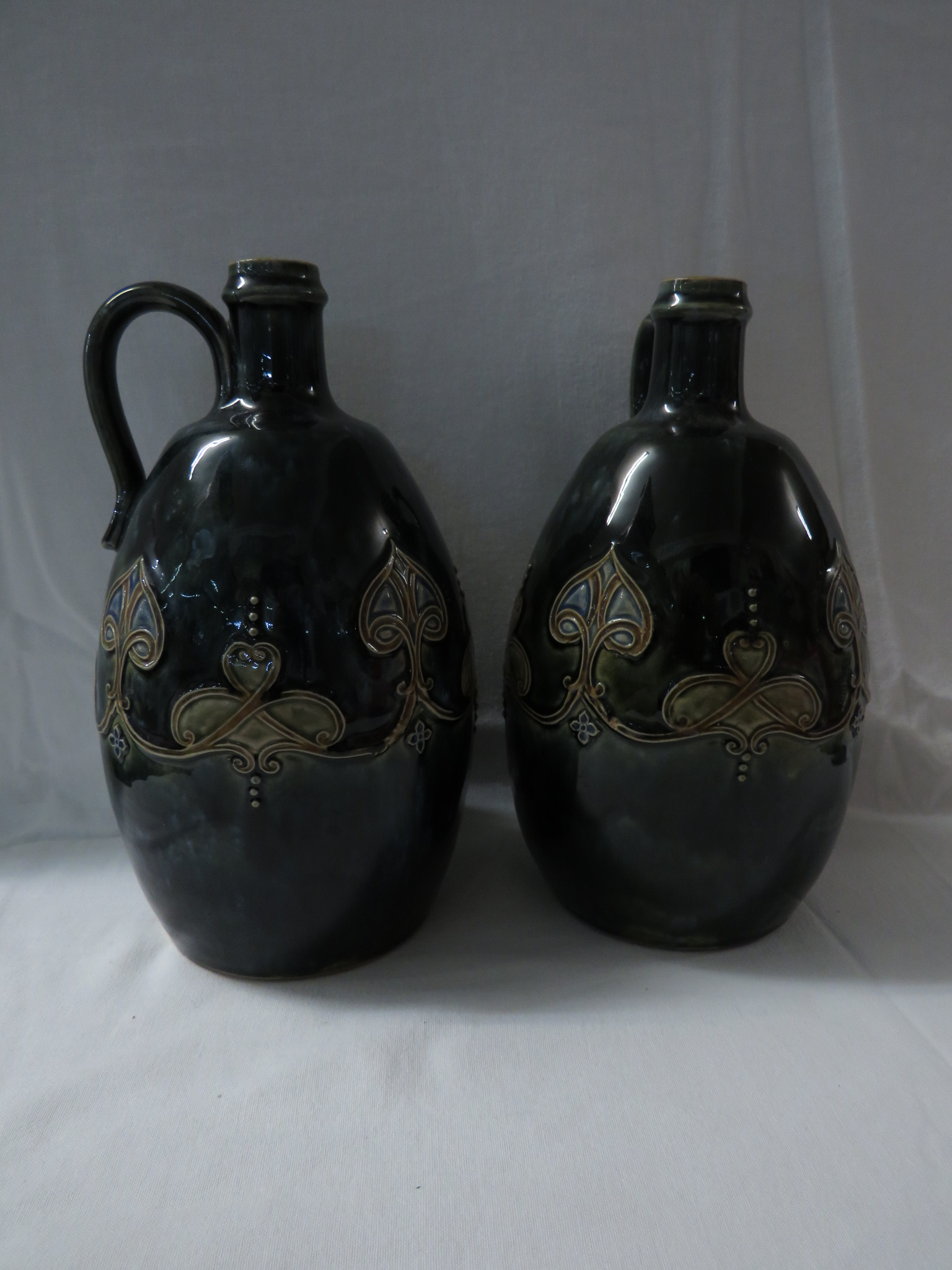 Lot 51 - Pair of Royal Doulton stoneware bottles or pitchers of ovoid shape with loop handles at the neck,