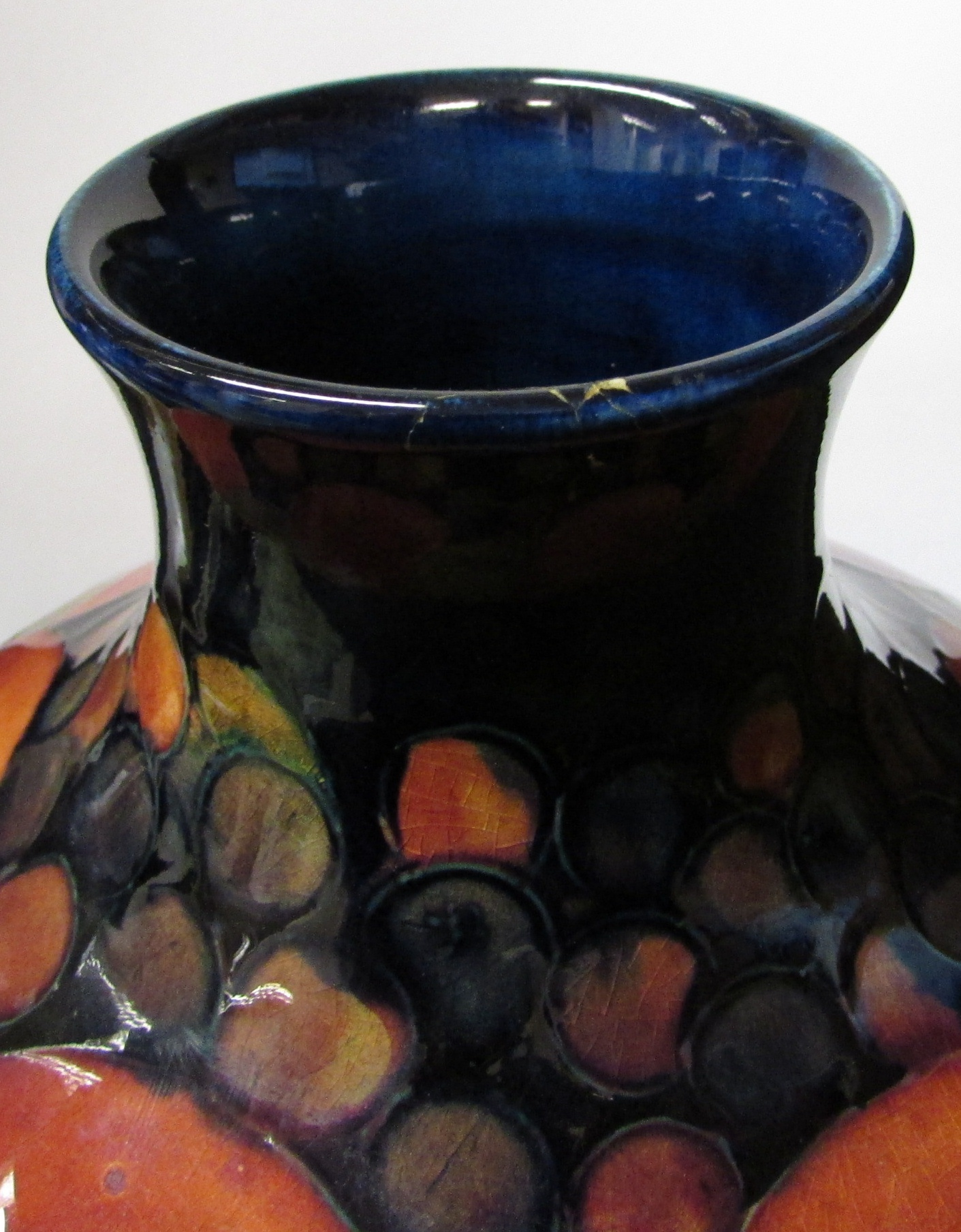 Lot 8 - Moorcroft pottery pomegranate vase of squat form, dark blue ground, the base stamped MOORCROFT