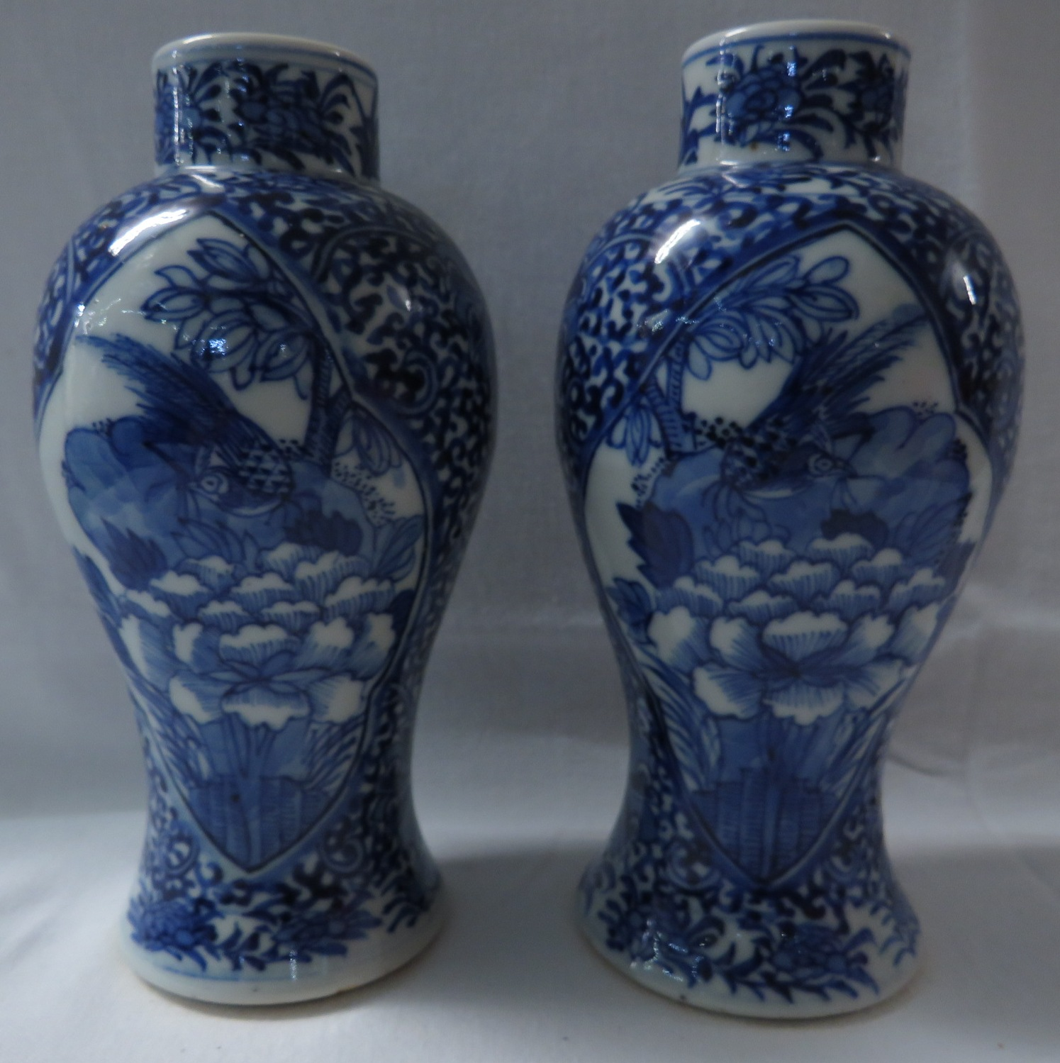 Lot 35 - A pair of Chinese porcelain baluster vases hand painted in underglaze blue with scrolled foliage and