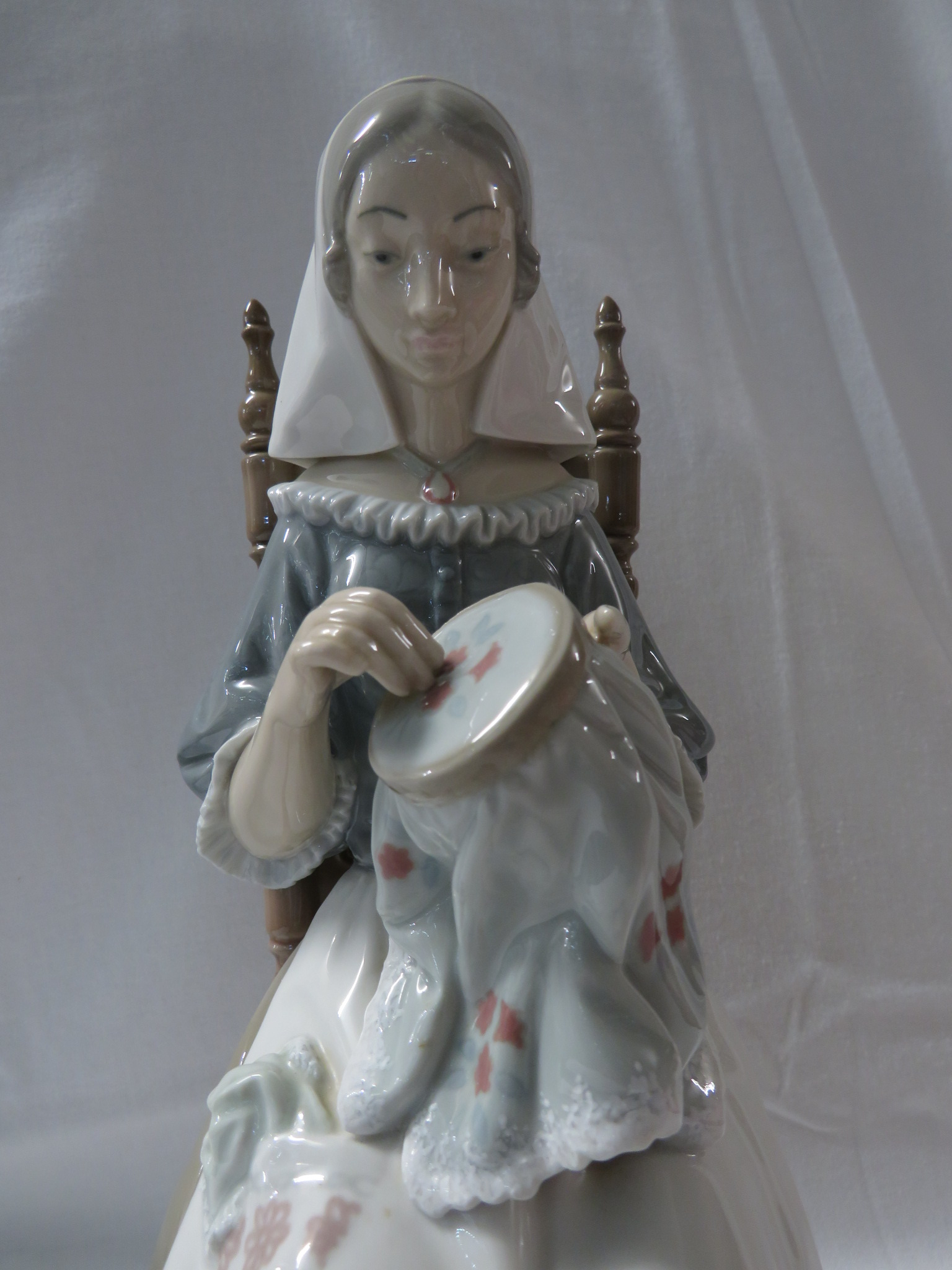 Lot 56 - Lladro porcelain figure of a woman with embroidery seated on a spindle turned chair (height 28cm)