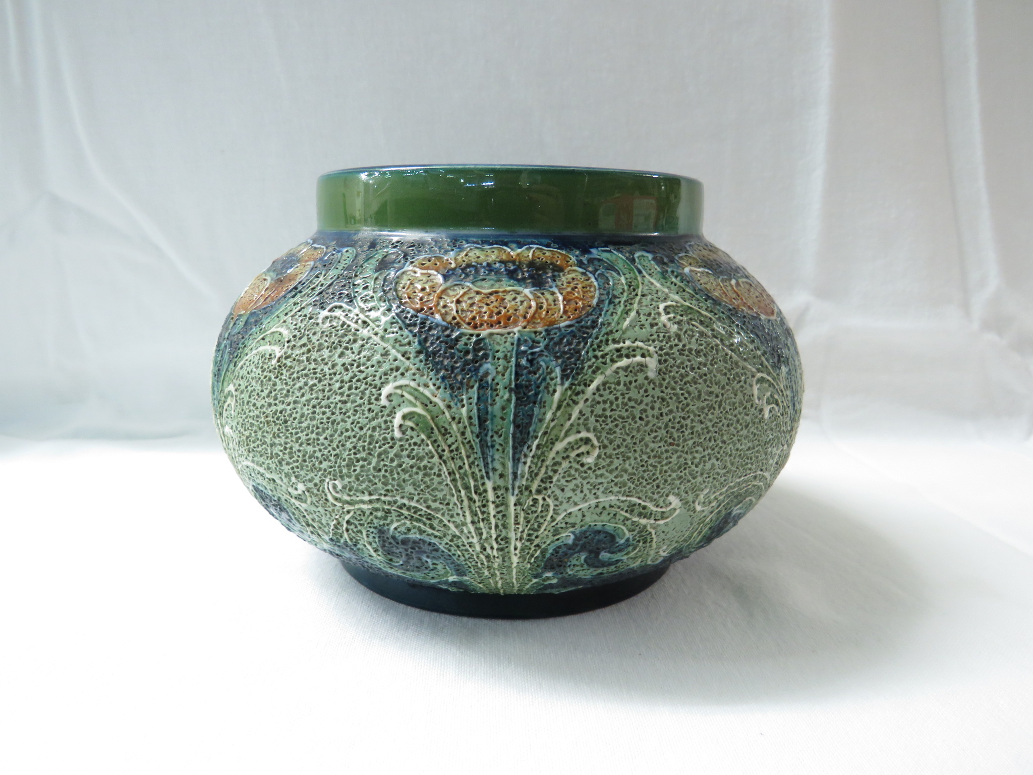 Lot 11 - Macintyre JM & Co squat pottery vase, blue and green textured glaze with a repeating pattern of