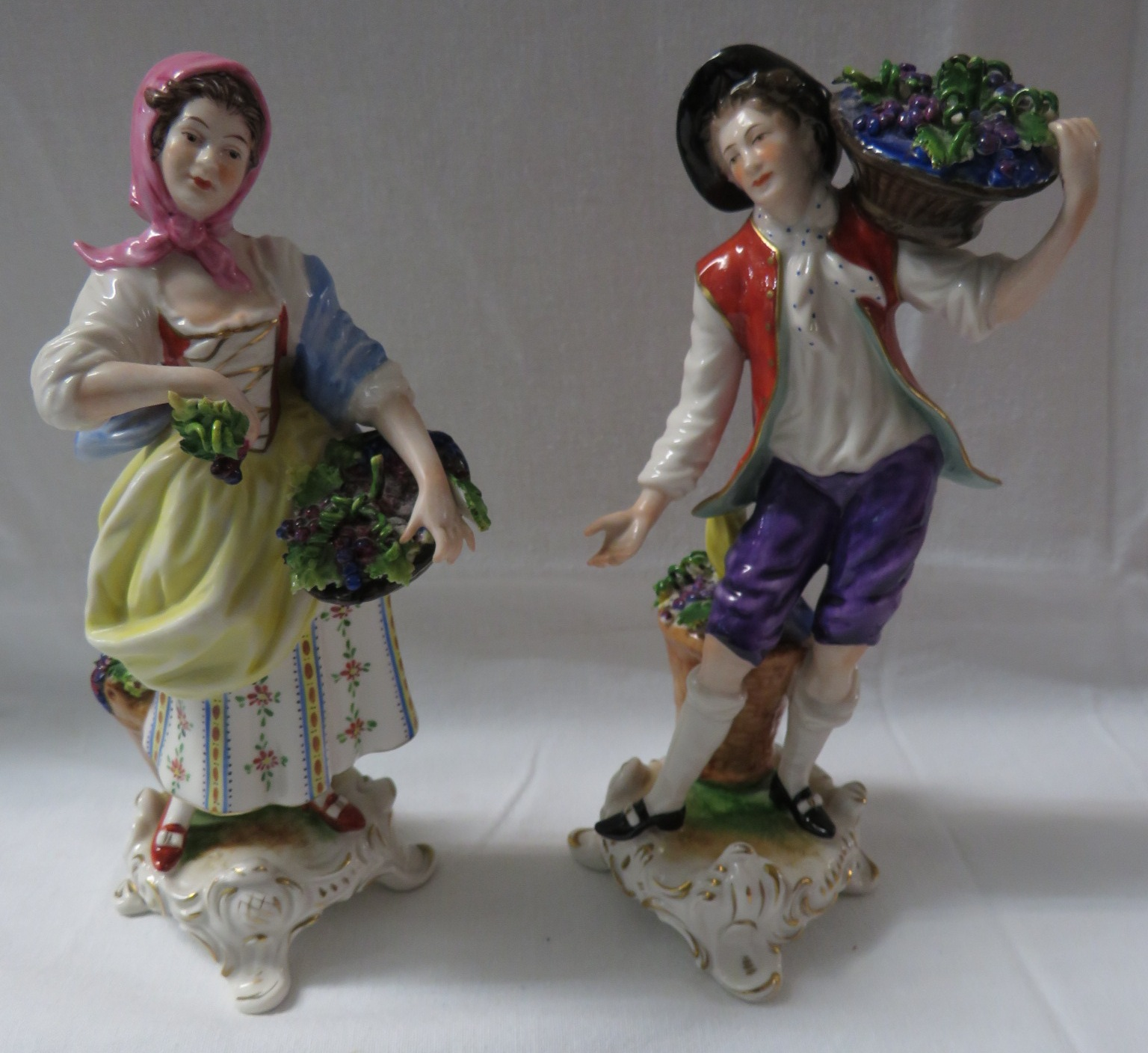 Lot 26A - A matched pair of Rudolf Kammer porcelain figures of grape pickers, man and woman, each on