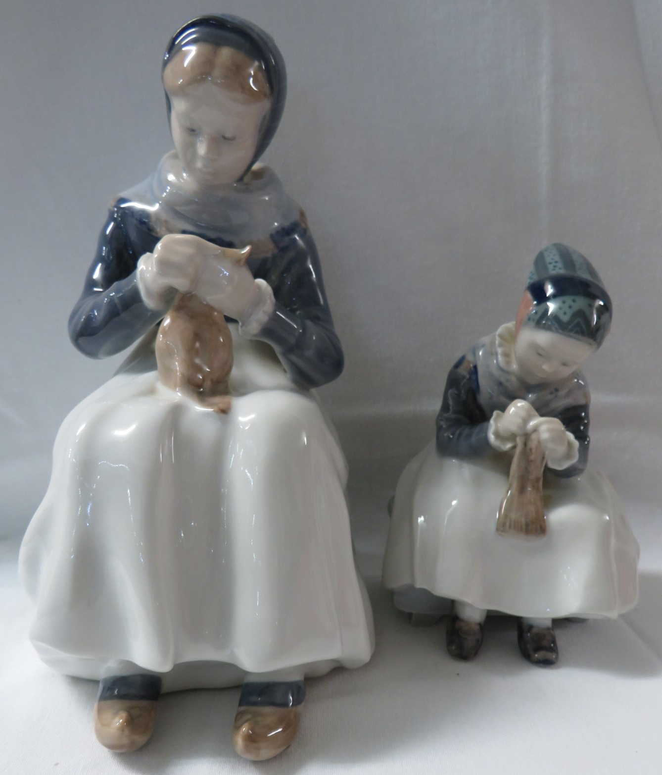 Lot 57 - Two Royal Copenhagen figures - a young woman seated on a bench with sewing, numbered 1317, height