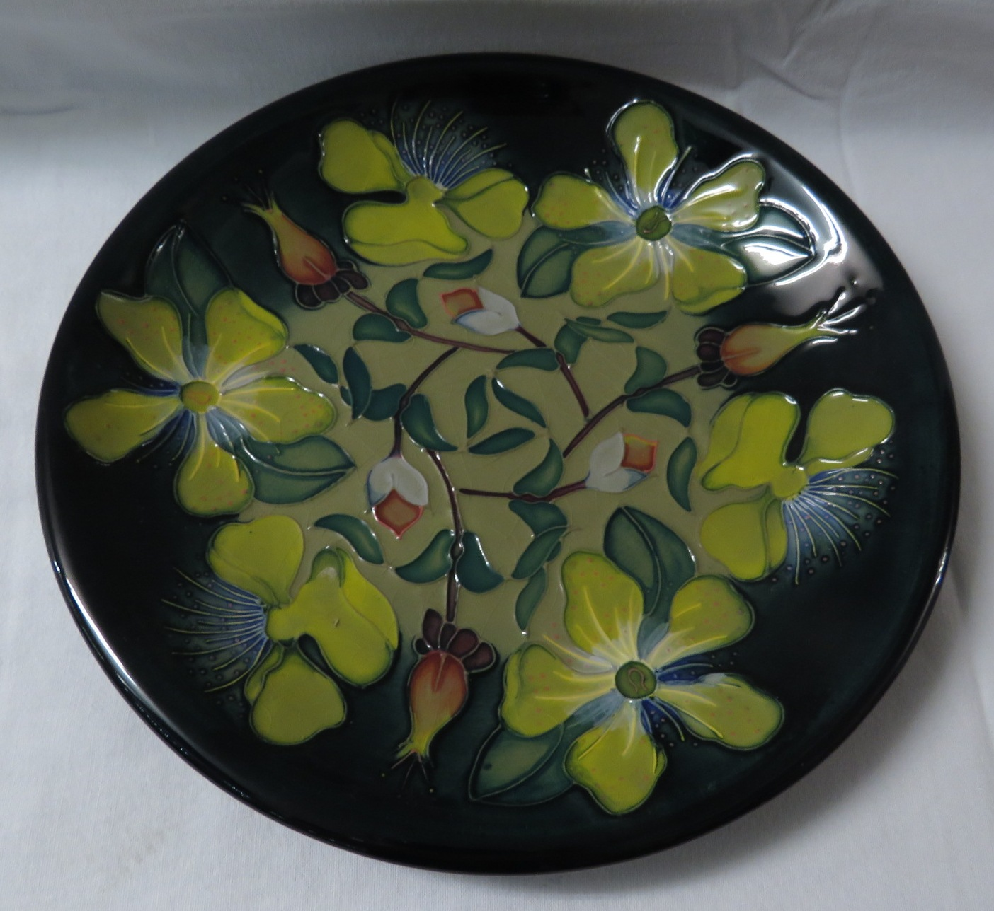 Lot 7 - Moorcroft pottery dish, yellow and green ground, dark blue green at edge, decorated with yellow