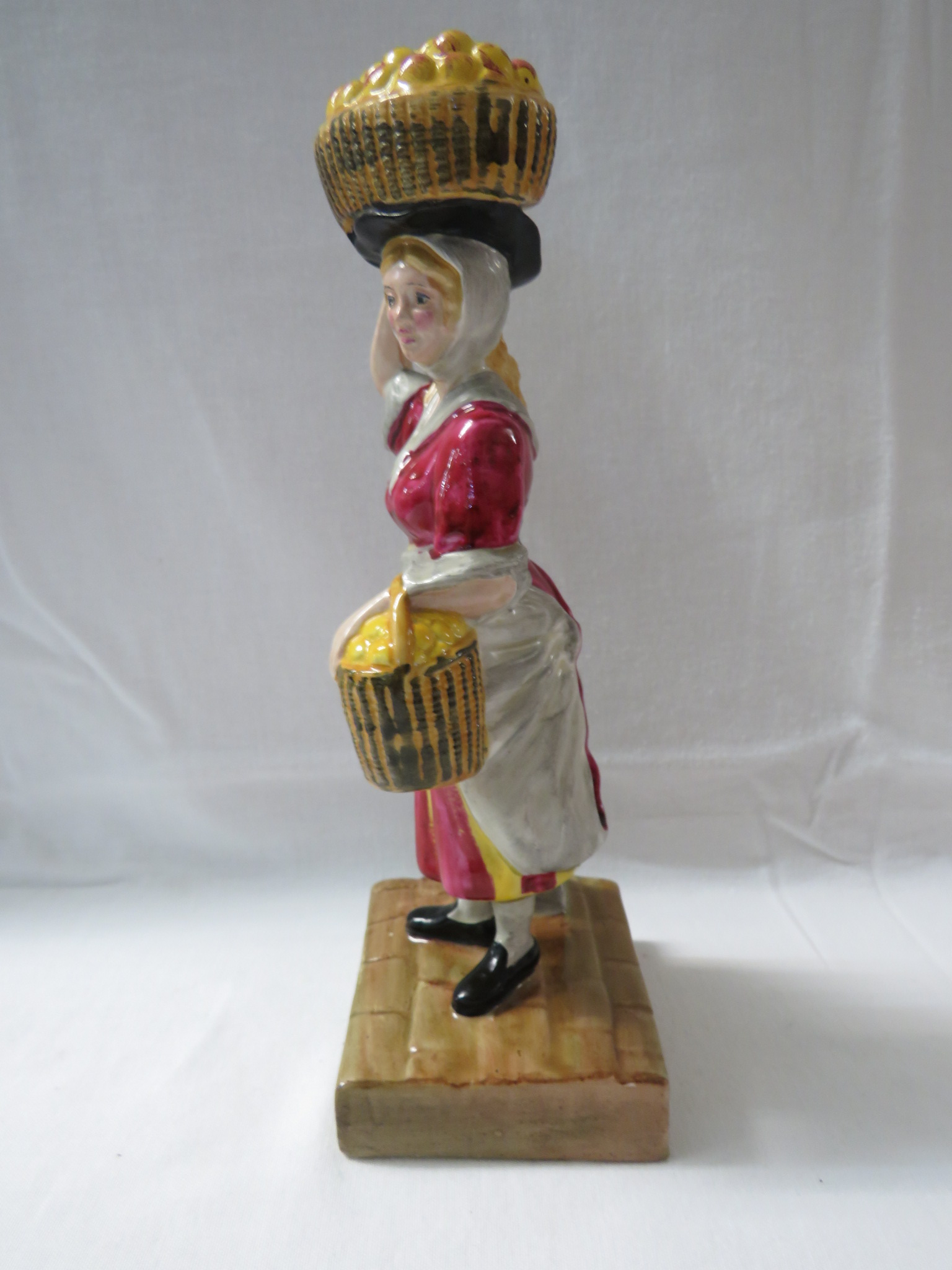 Lot 46 - Wilkinson Ltd Clarice Cliff pottery figure of woman street vendor with fruit baskets, the base