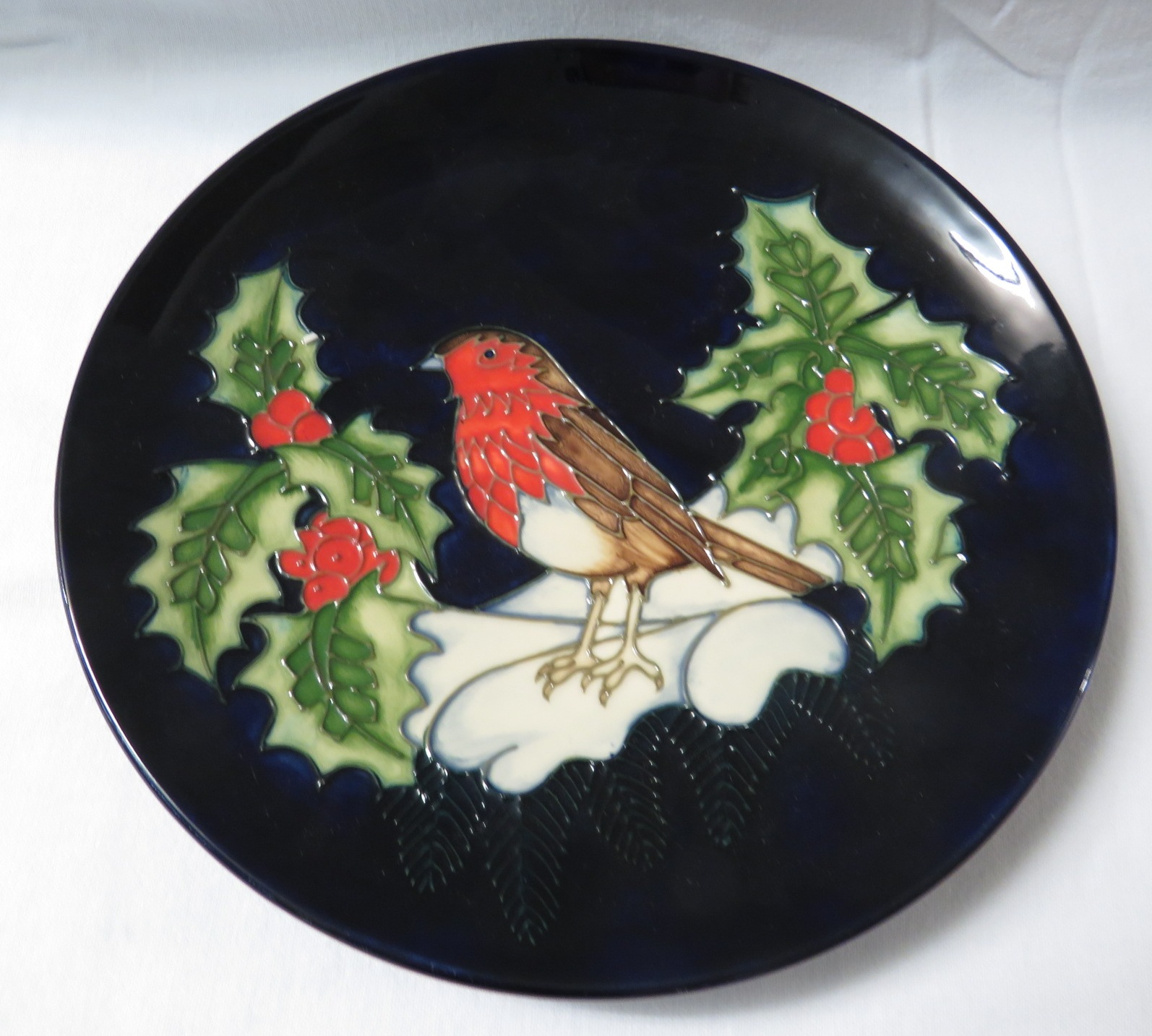 Lot 5 - Moorcroft pottery Christmas plate, dark blue with robin, holly and snow, stamped MOORCROFT MADE IN