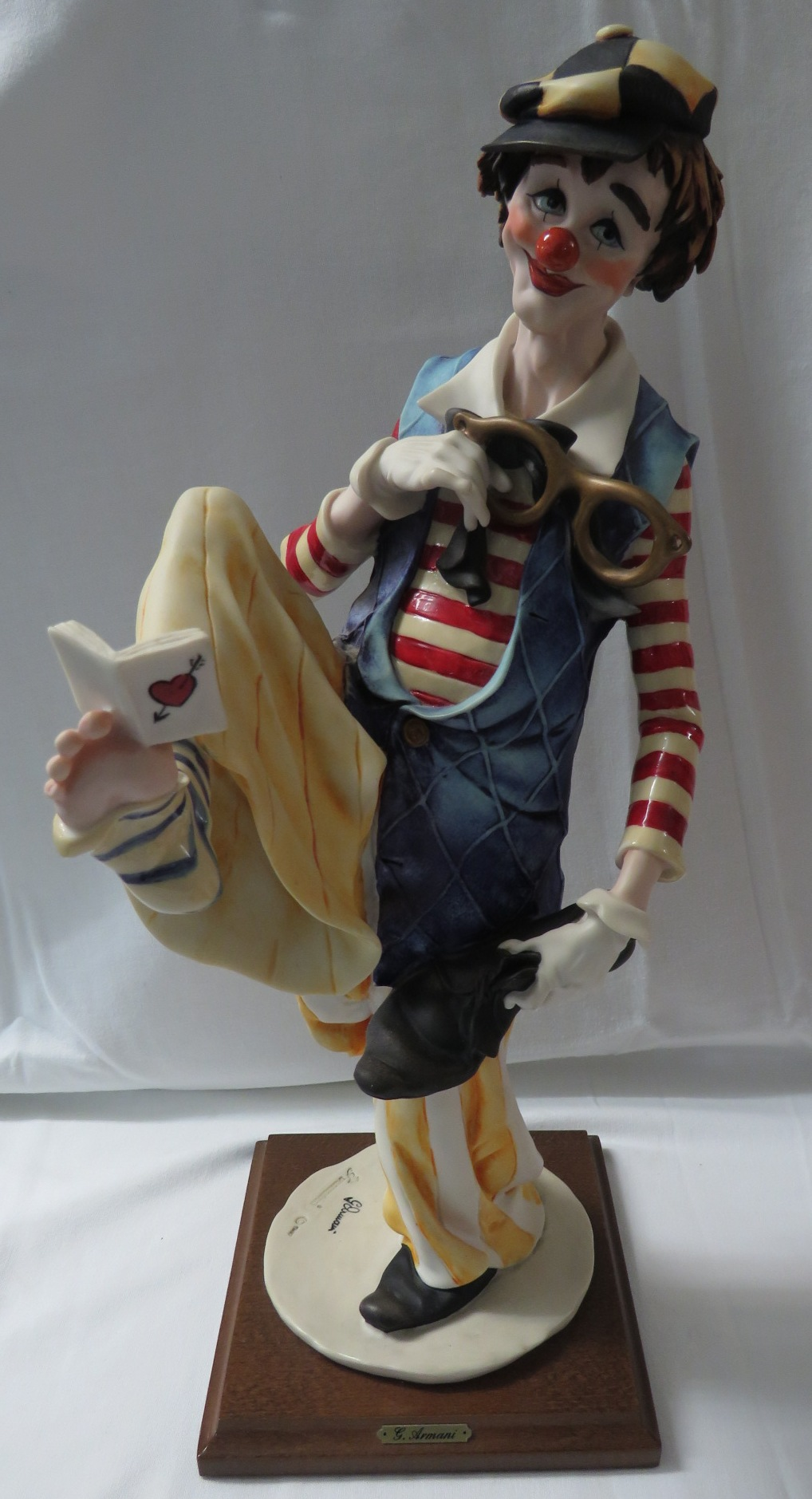 Lot 53 - A Capodimonte resin figure of a clown reading a book held between his toes, signed G Armani with