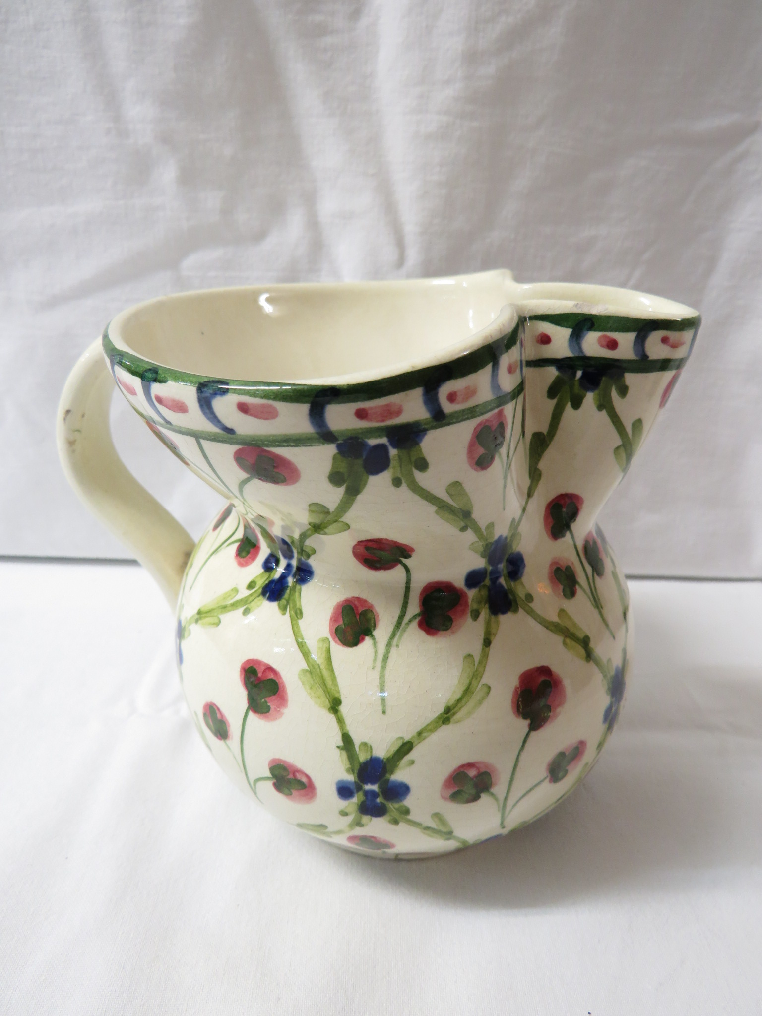 Lot 20 - A floral pottery milk jug marked Liberty London, cream ground and painted with a trellis pattern