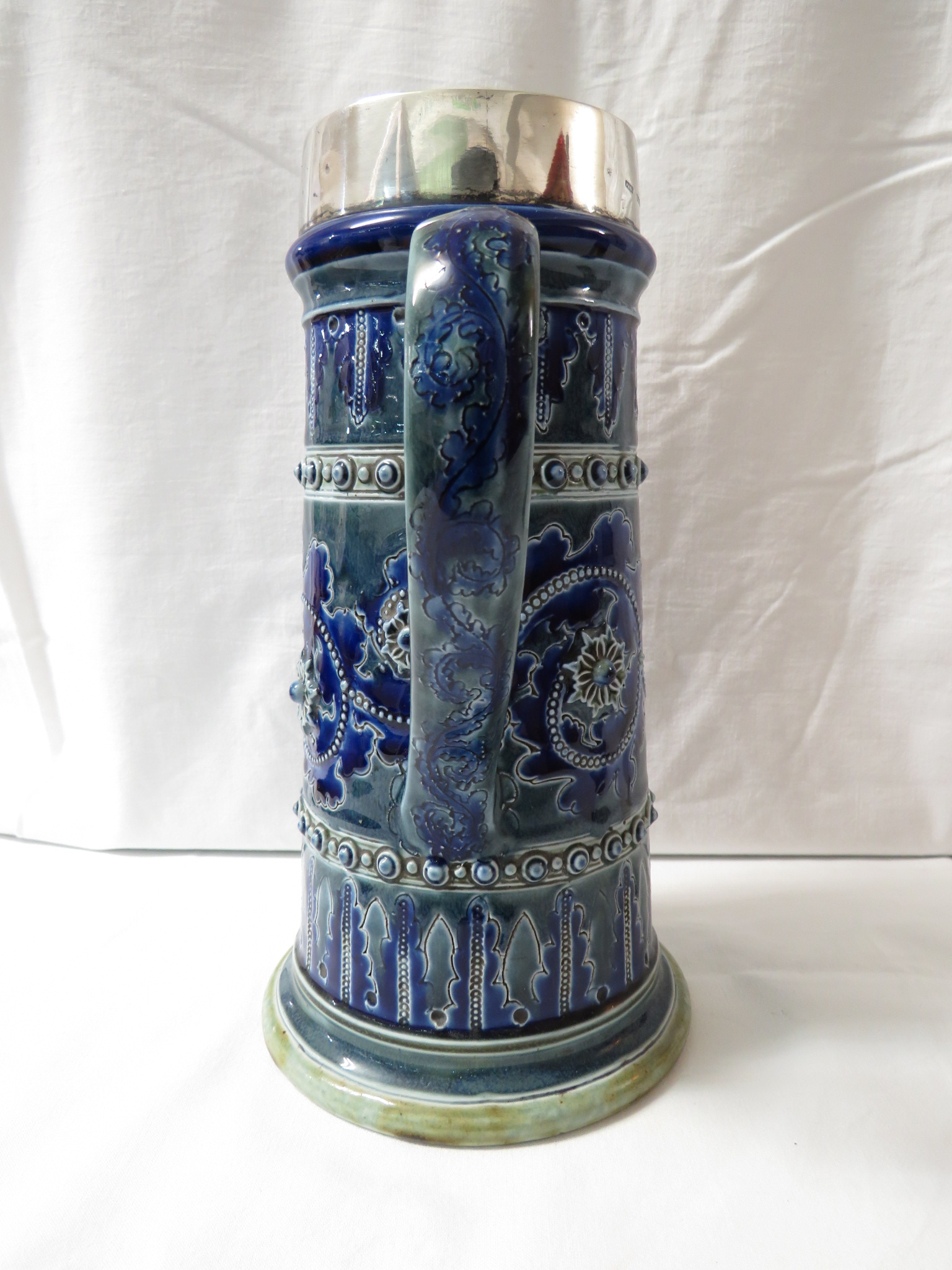 Lot 49 - Doulton Lambeth ewer of tapering cylindrical form with silver rim and spout, blue and green glaze