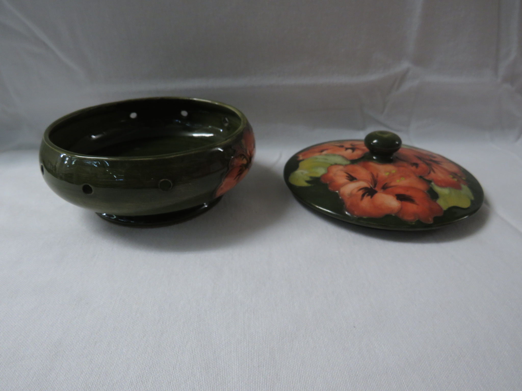 Lot 9 - Moorcroft pottery pot pourri jar, green ground with pink hibiscus, stamped MOORCROFT and paper