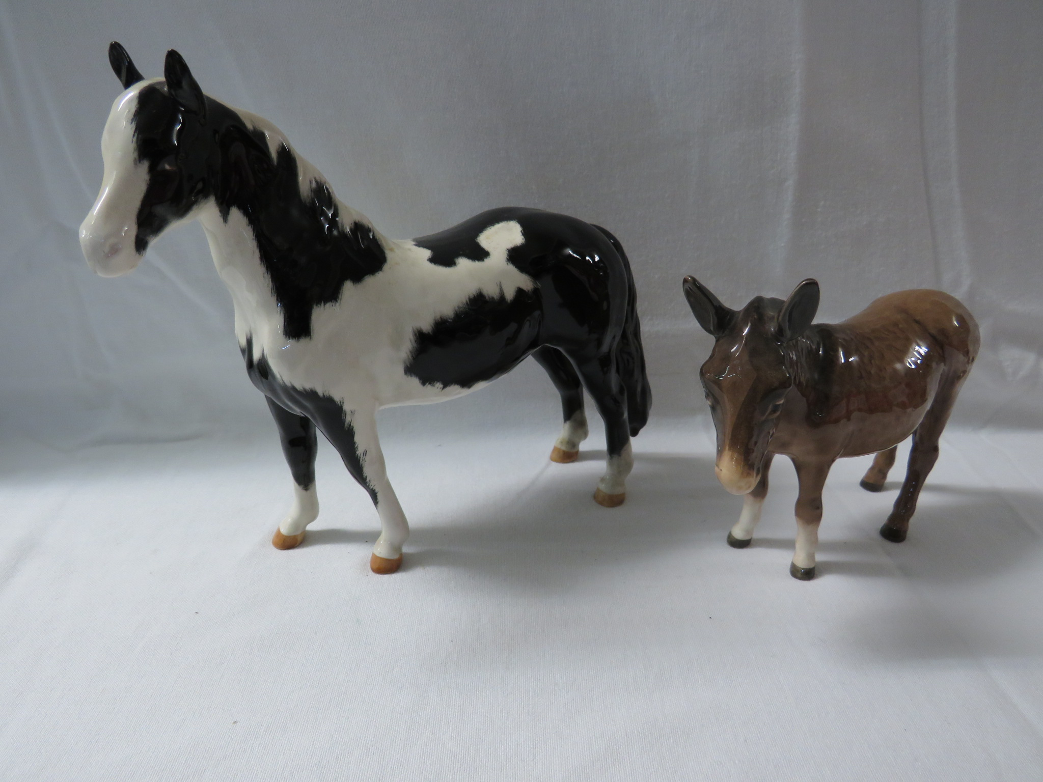 Lot 44 - Five Beswick equestrian models - a Dartmoor pony, an Exmoor pony, a brown horse, a black and white