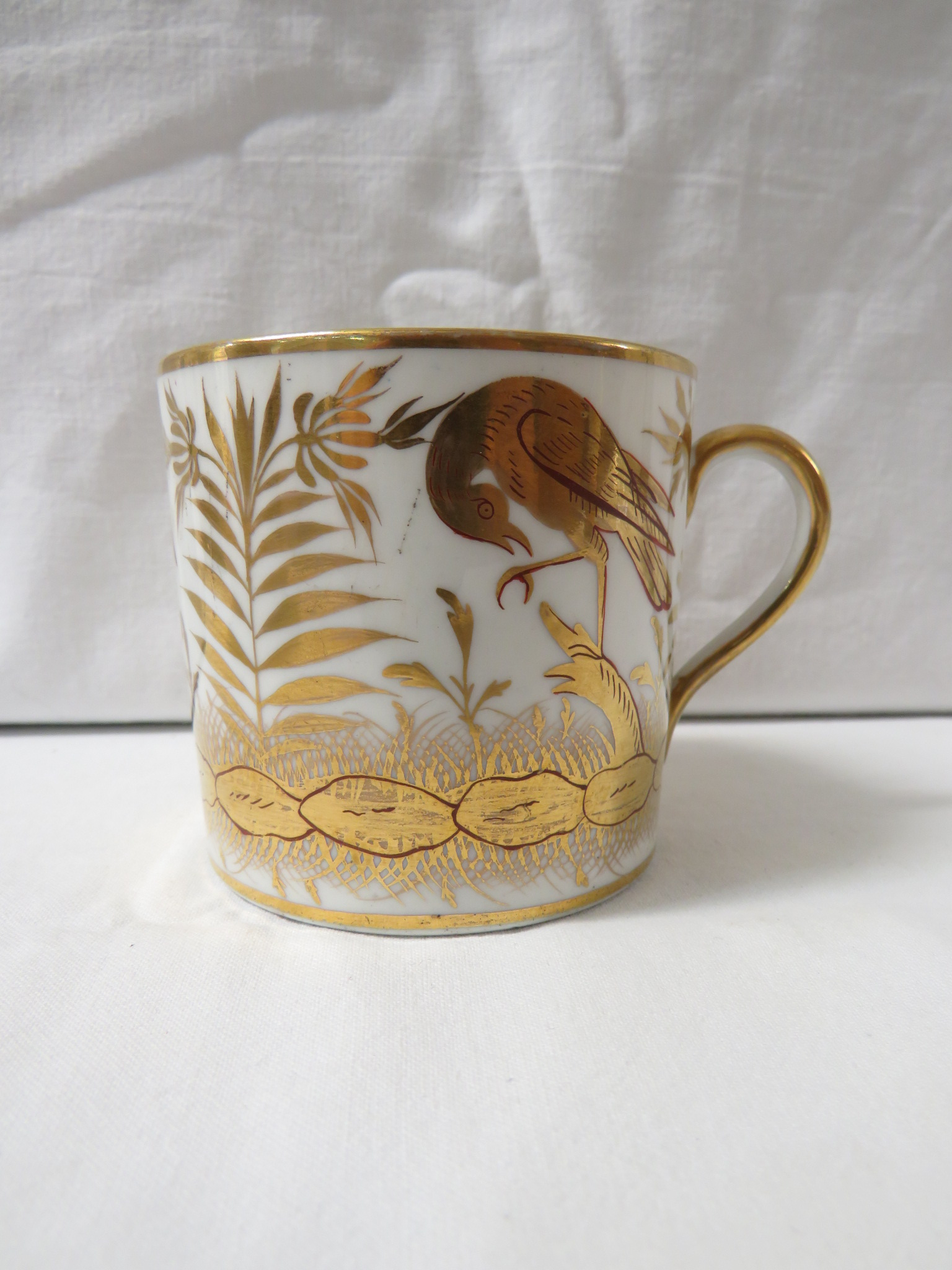 Lot 45 - A 19th century porcelain cup and saucer gilded with birds and flowers