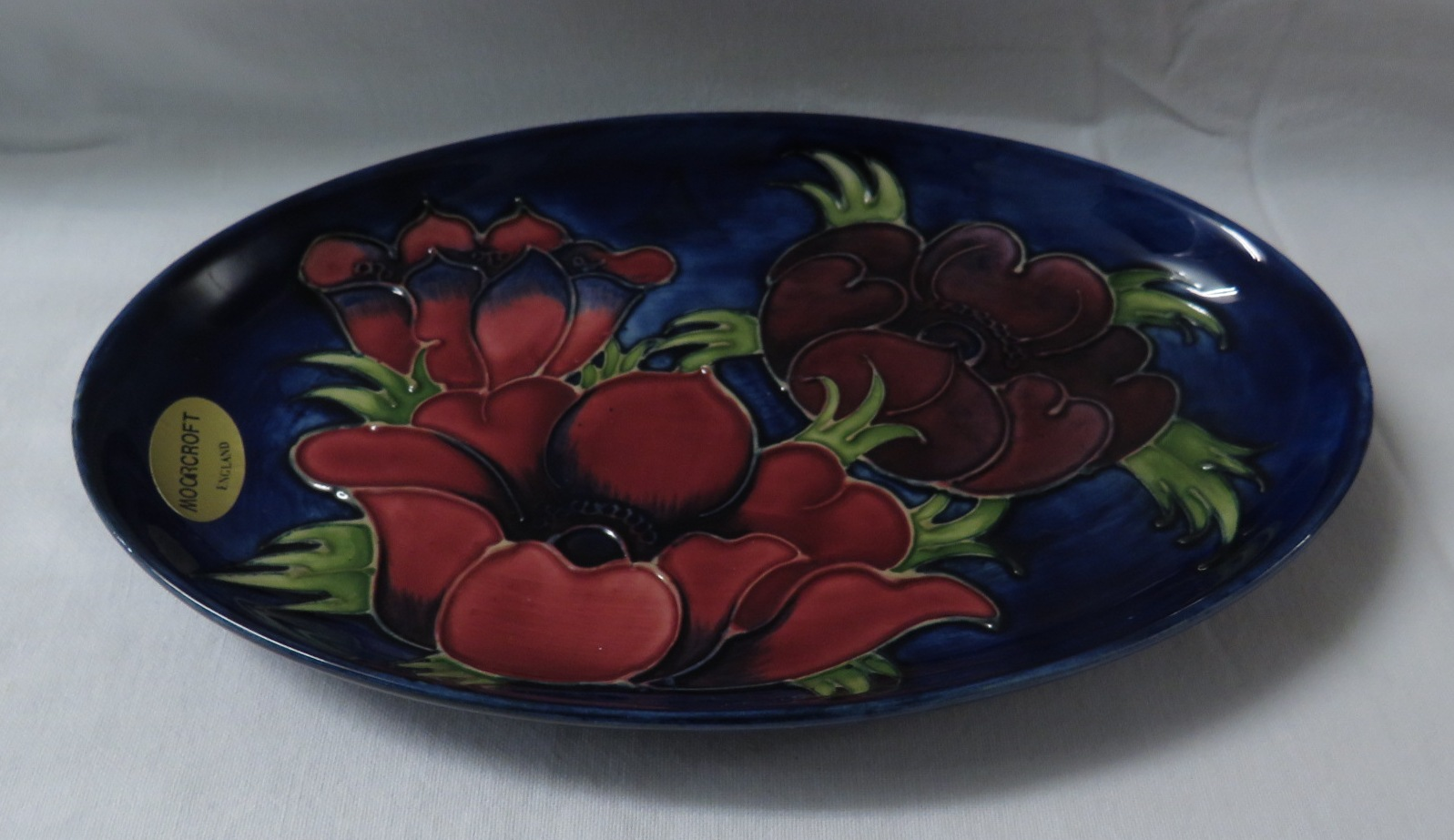 Lot 10 - Moorcroft pottery oval dish, blue ground painted with red and maroon poppies, stamped MOORCROFT MADE