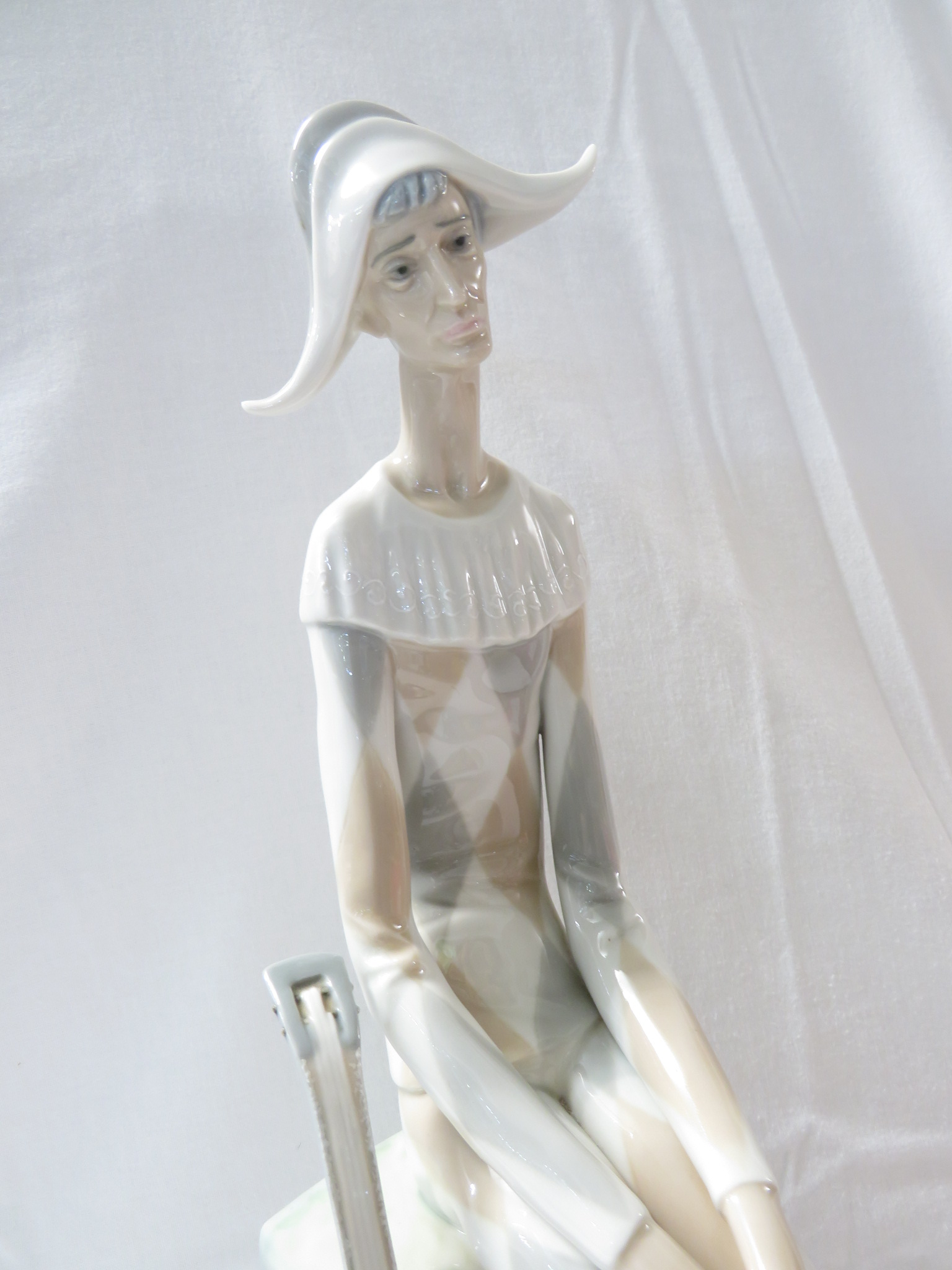 Lot 55 - Lladro porcelain figure of a long-limbed harlequin seated with mandolin (height 36cm)