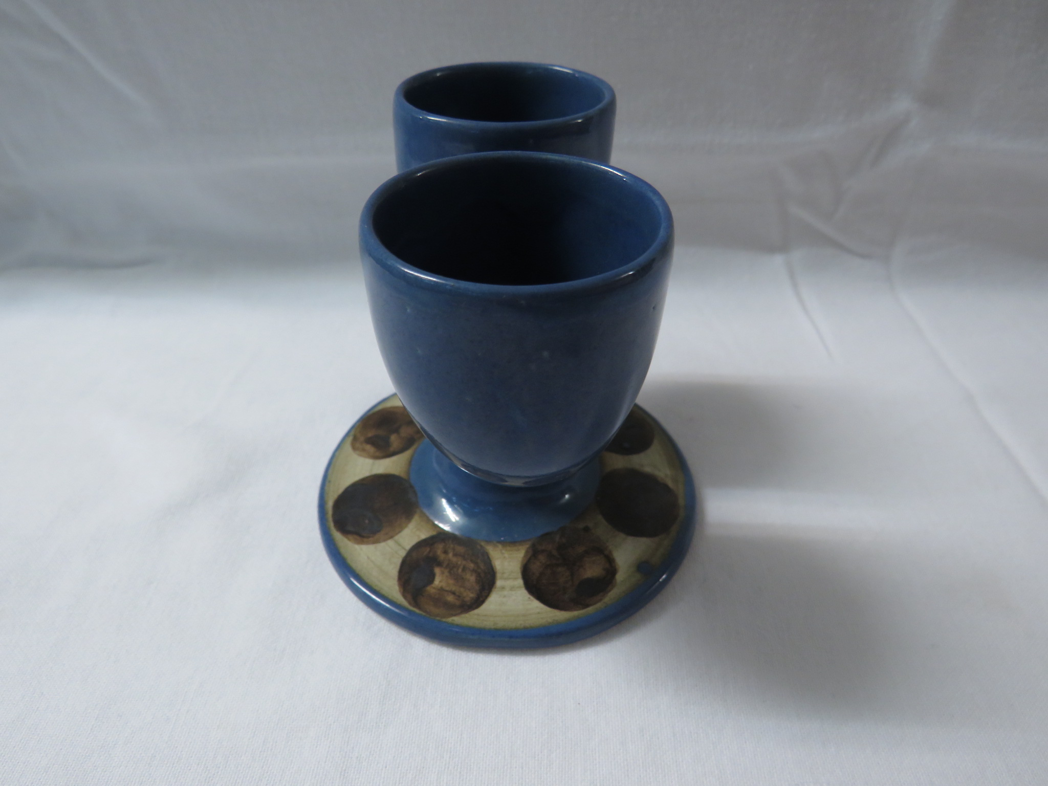 Lot 13 - Troika pottery double egg cup, blue glaze, the circular foot in fawn with painted brown discs, the