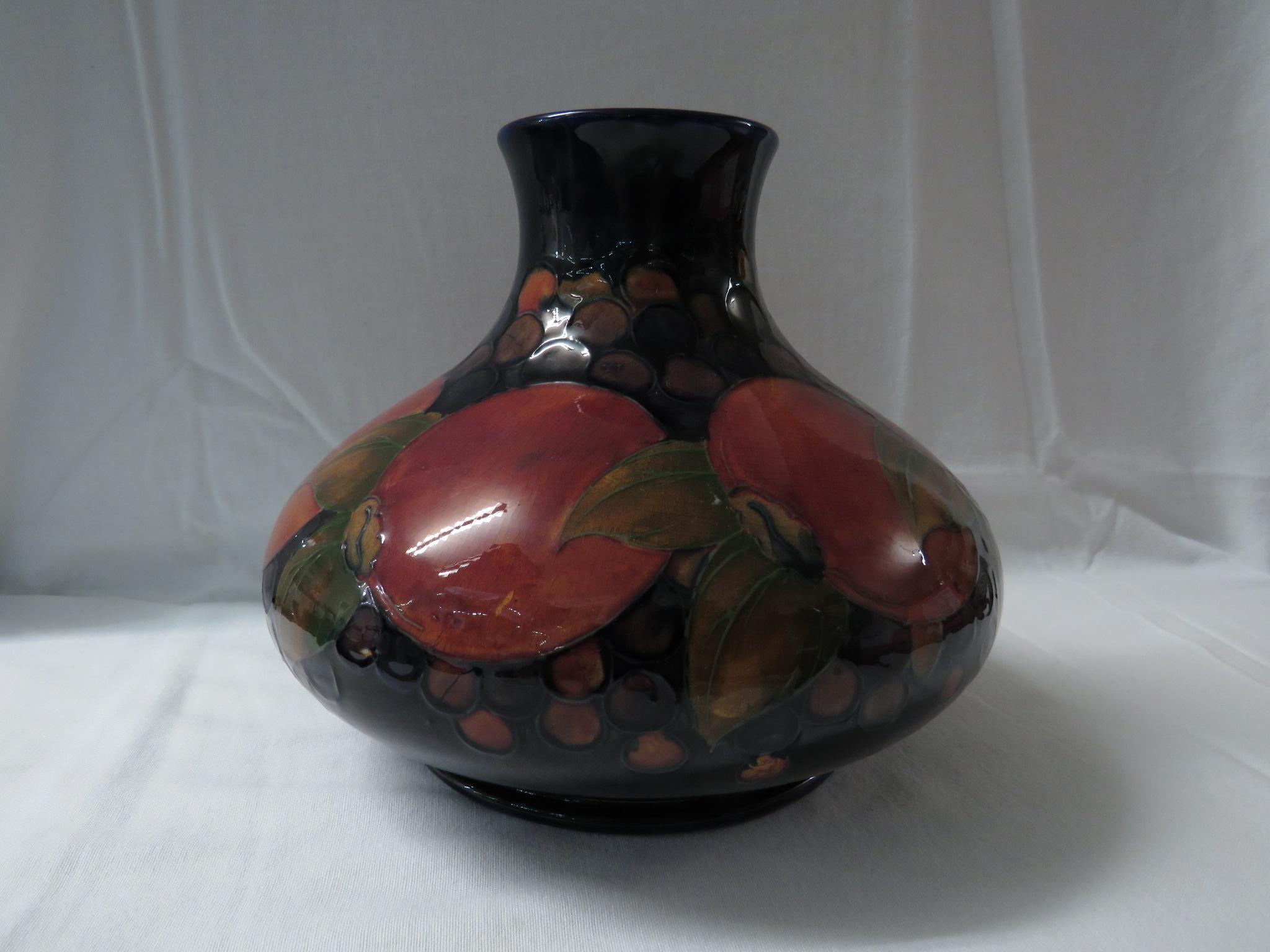 Lot 8 - Moorcroft pottery pomegranate vase of squat form, dark blue ground, the base stamped MOORCROFT