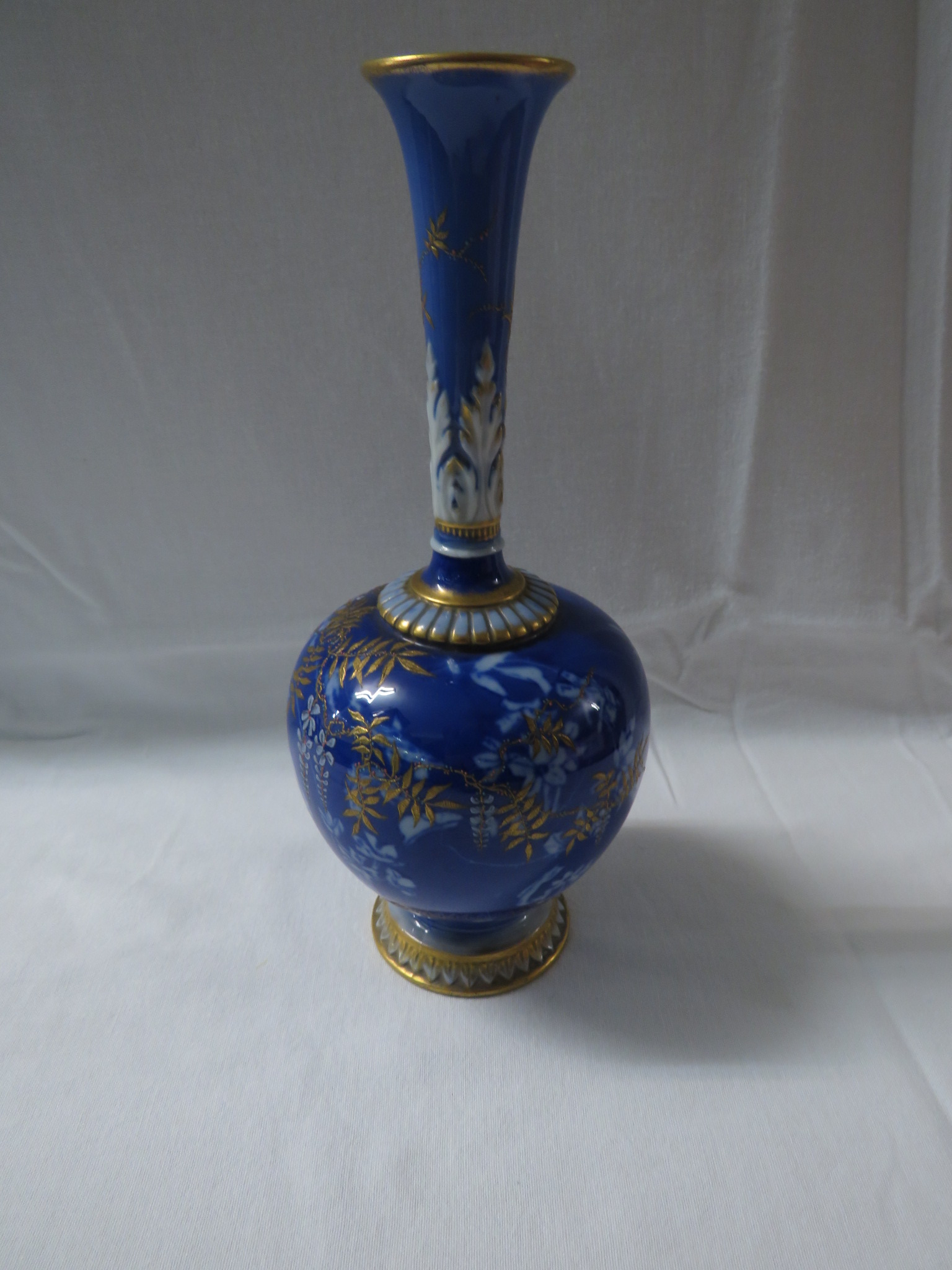 Lot 14 - A Royal Worcester porcelain vase of bottle shape with slender neck moulded with acanthus,