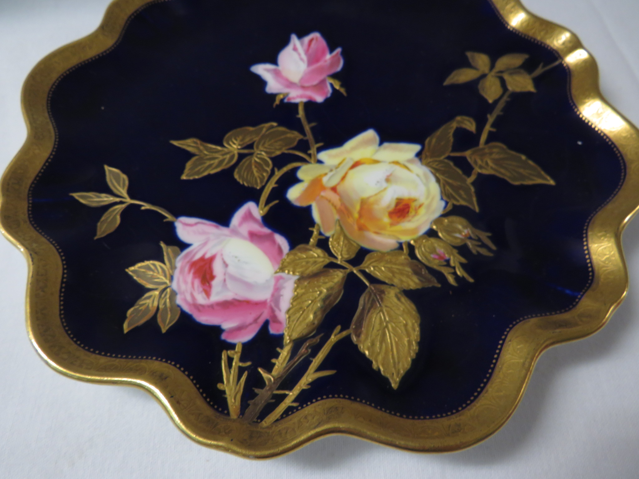 Lot 28 - A porcelain plate with wavy edge and gilt rim, cobalt blue ground and painted and gilded with pink