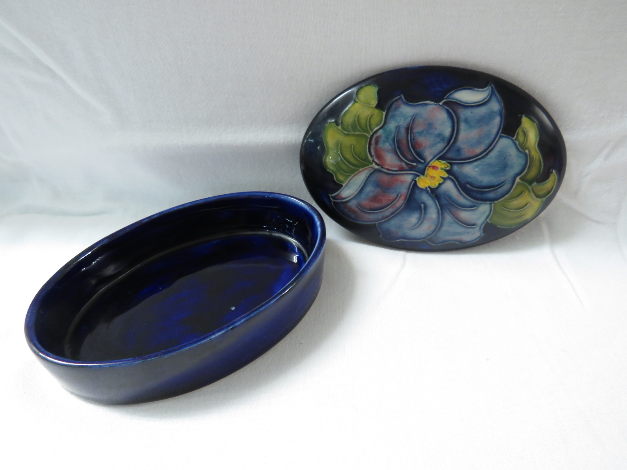 Lot 3 - Moorcroft pottery oval lidded box, dark blue ground, the lid decorated with a blue flower, the