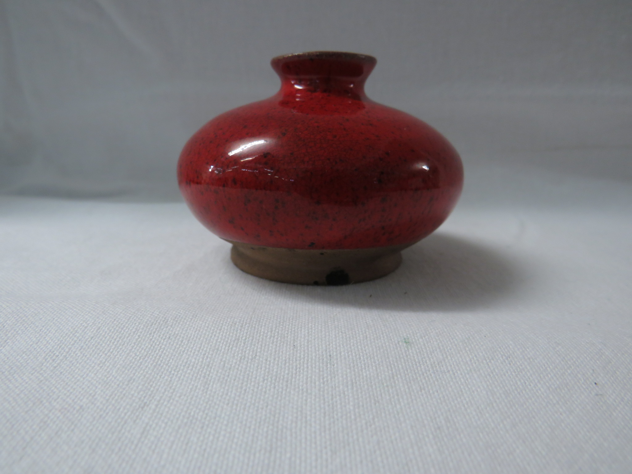 Lot 34 - A Ming style terracotta vase or pot of squat form in a bright red mottled glaze falling short of the
