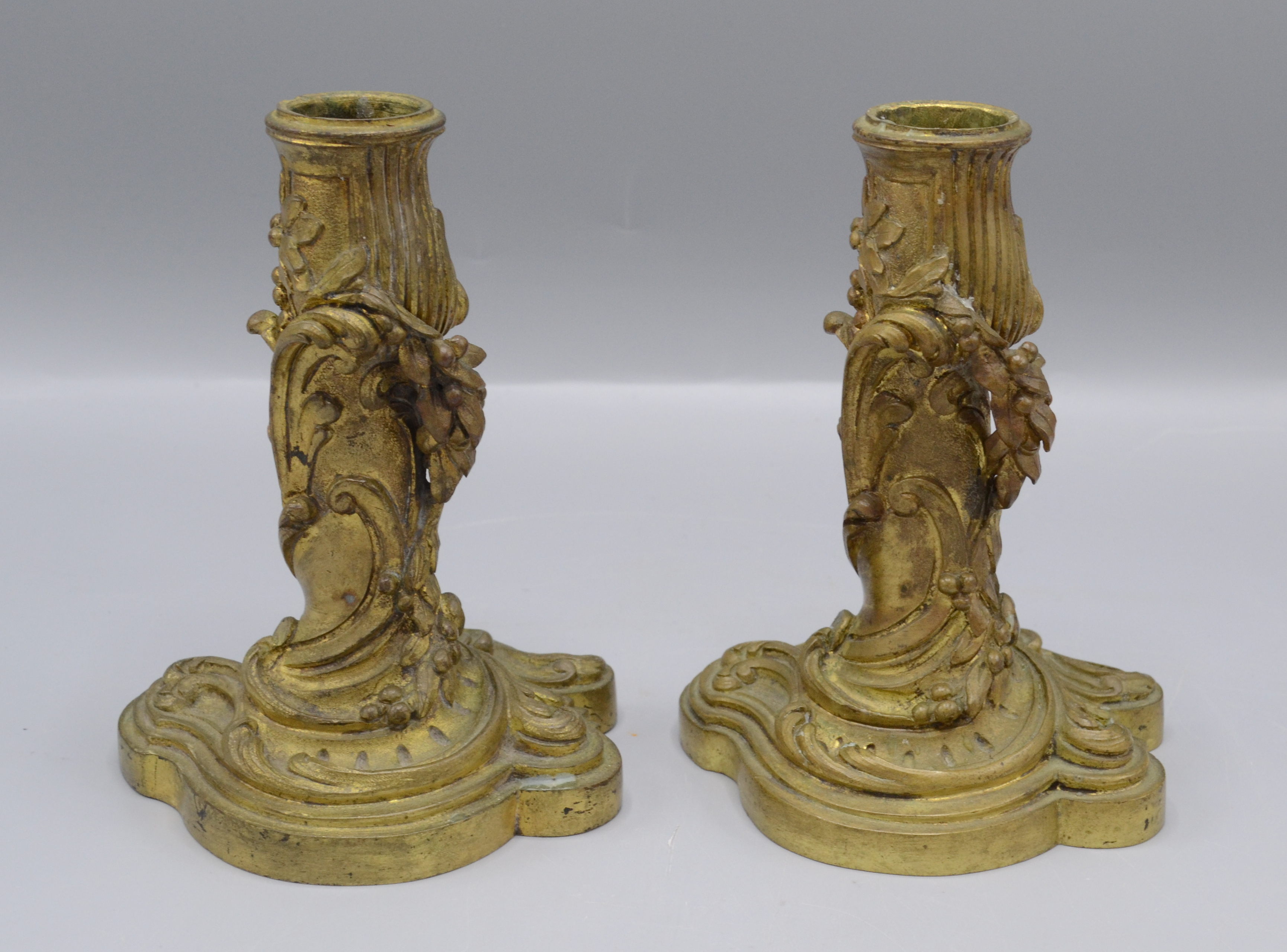 Lot 47 - A pair of continental gilt metal candlesticks, the body decorated with leaves and floral swags,