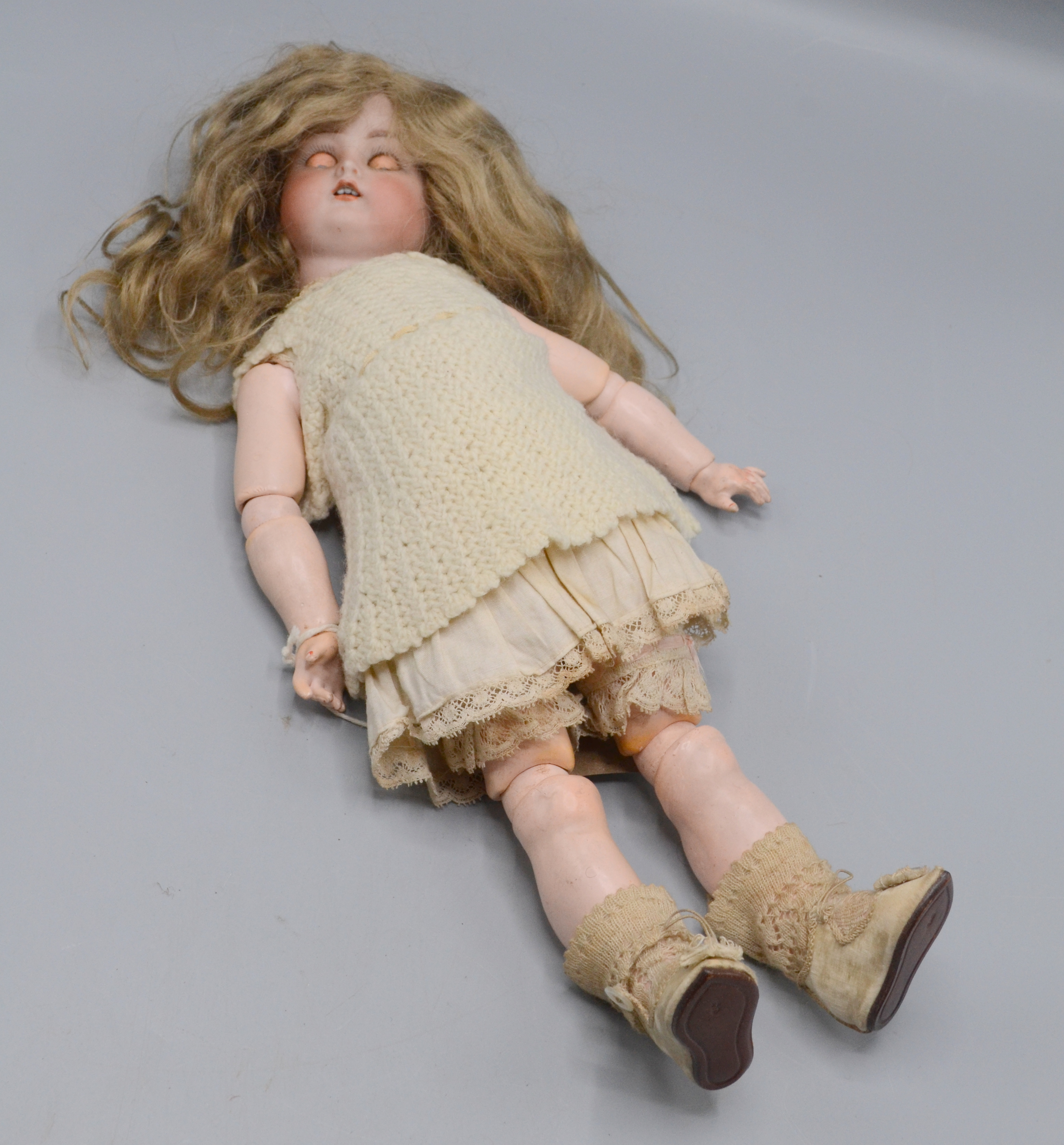 Lot 37 - A doll with a bisque porcelain head, articulated arms and legs, length 34.