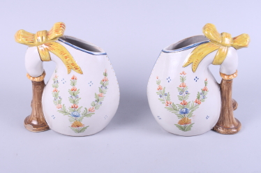 Lot 20 - A pair of early 20th century Quimper pottery jugs, naively painted with figures playing