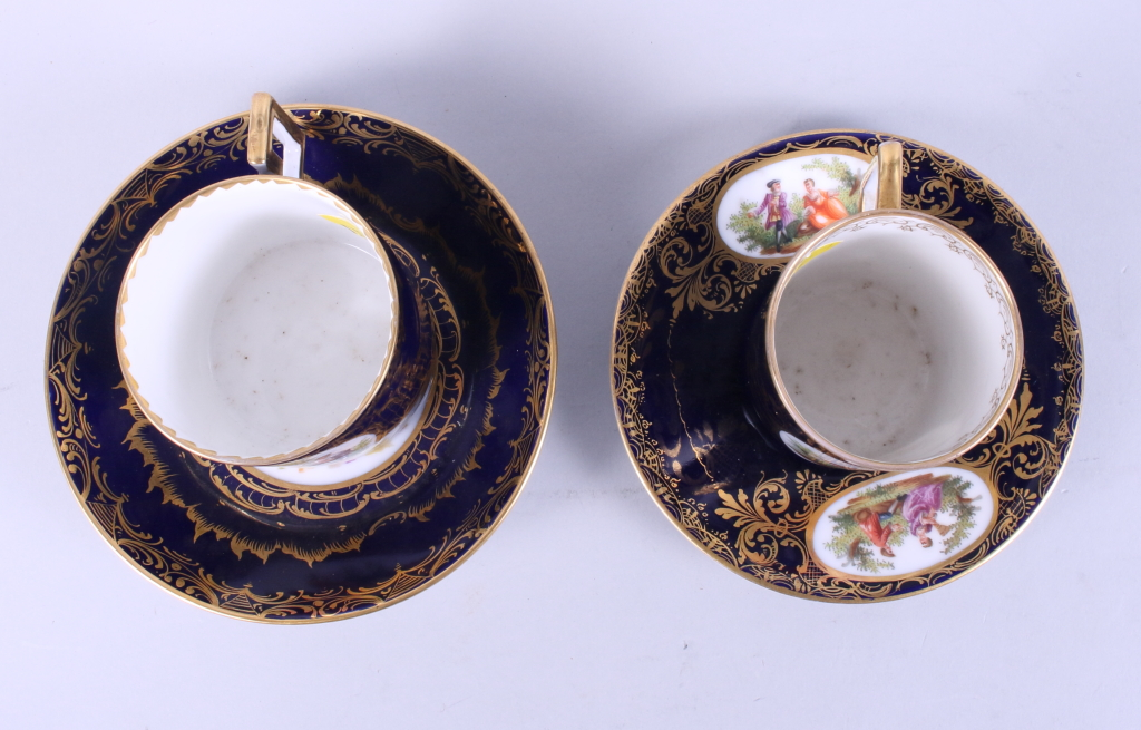 Lot 5 - Two Vienna porcelain coffee cans and saucers decorated figures on a blue ground with gilt