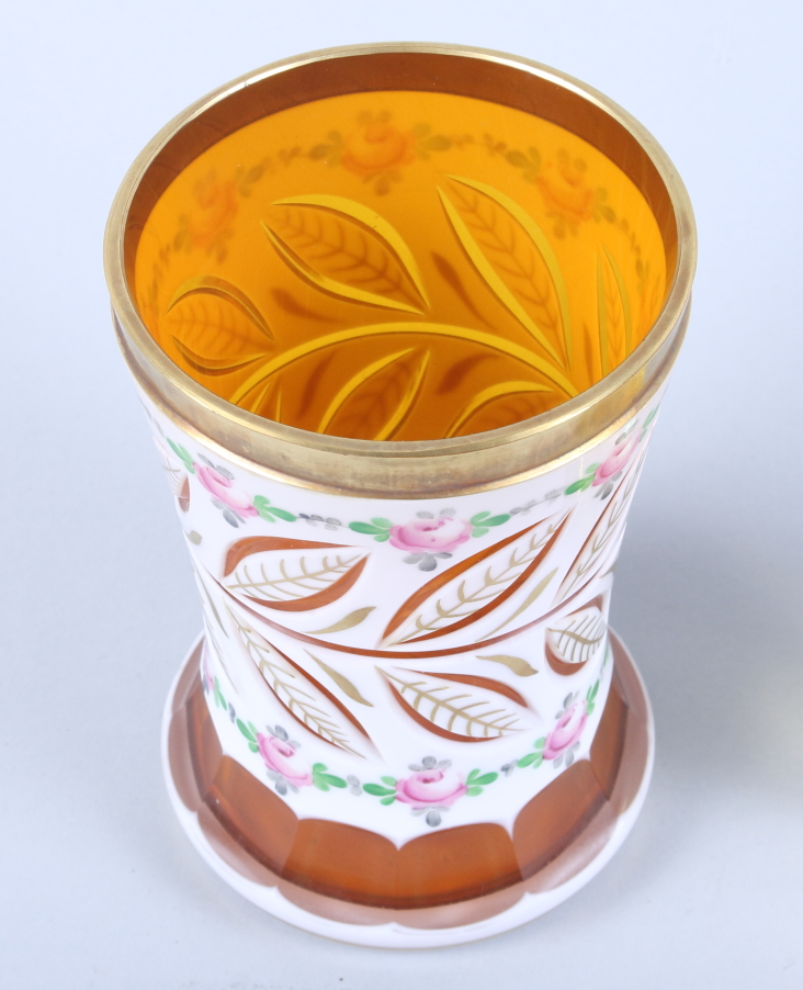 """Lot 53 - An early 20th century enamelled and gilt faceted Bohemian glass waisted beaker, 5 1/4"""" high, an"""
