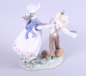 "Lot 27 - A Lladro figure of a girl and a scarecrow in a pumpkin patch, 10"" high"
